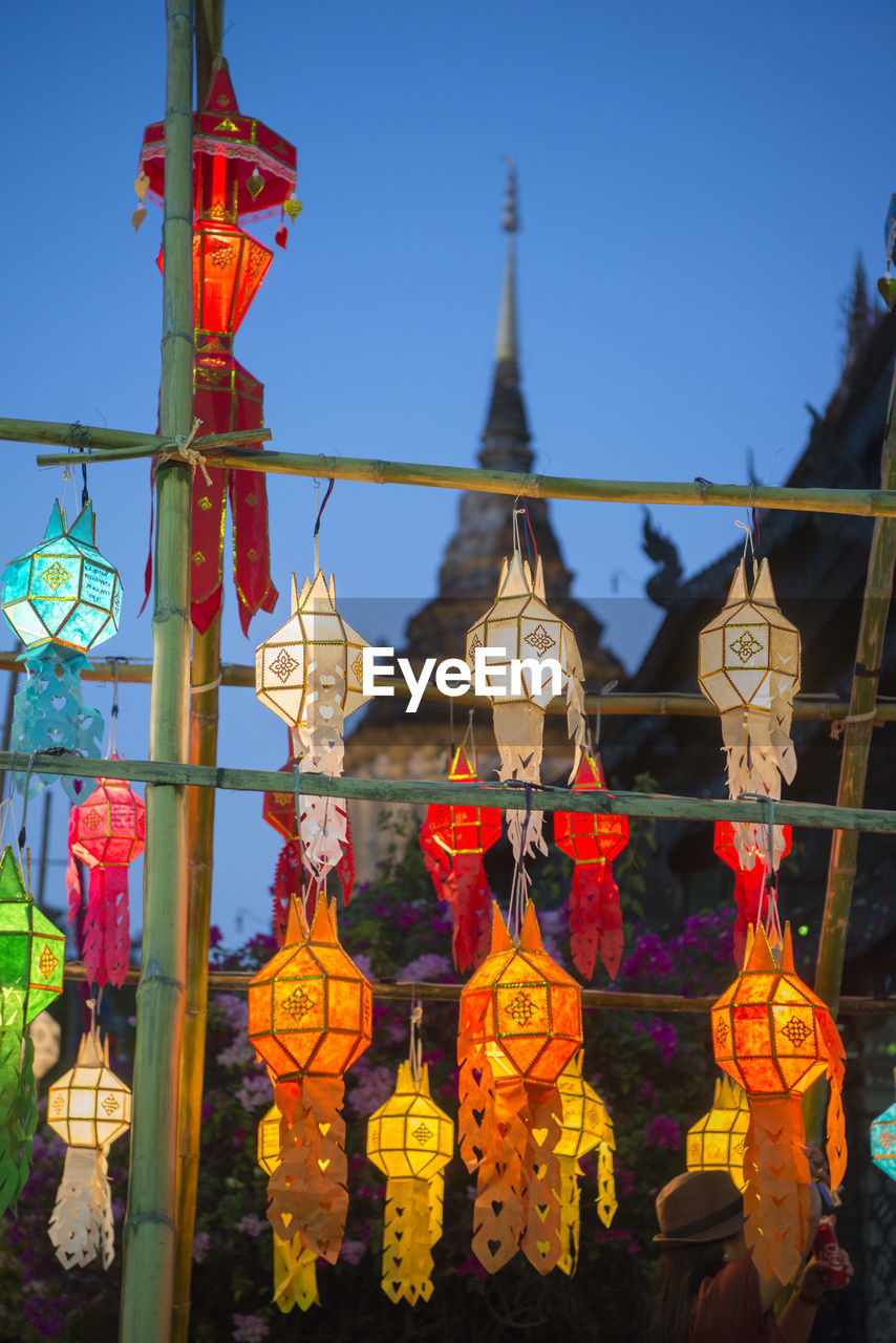 hanging, no people, cultures, lantern, focus on foreground, tradition, lighting equipment, outdoors, religion, day, close-up, low angle view, spirituality, clear sky, red, sky