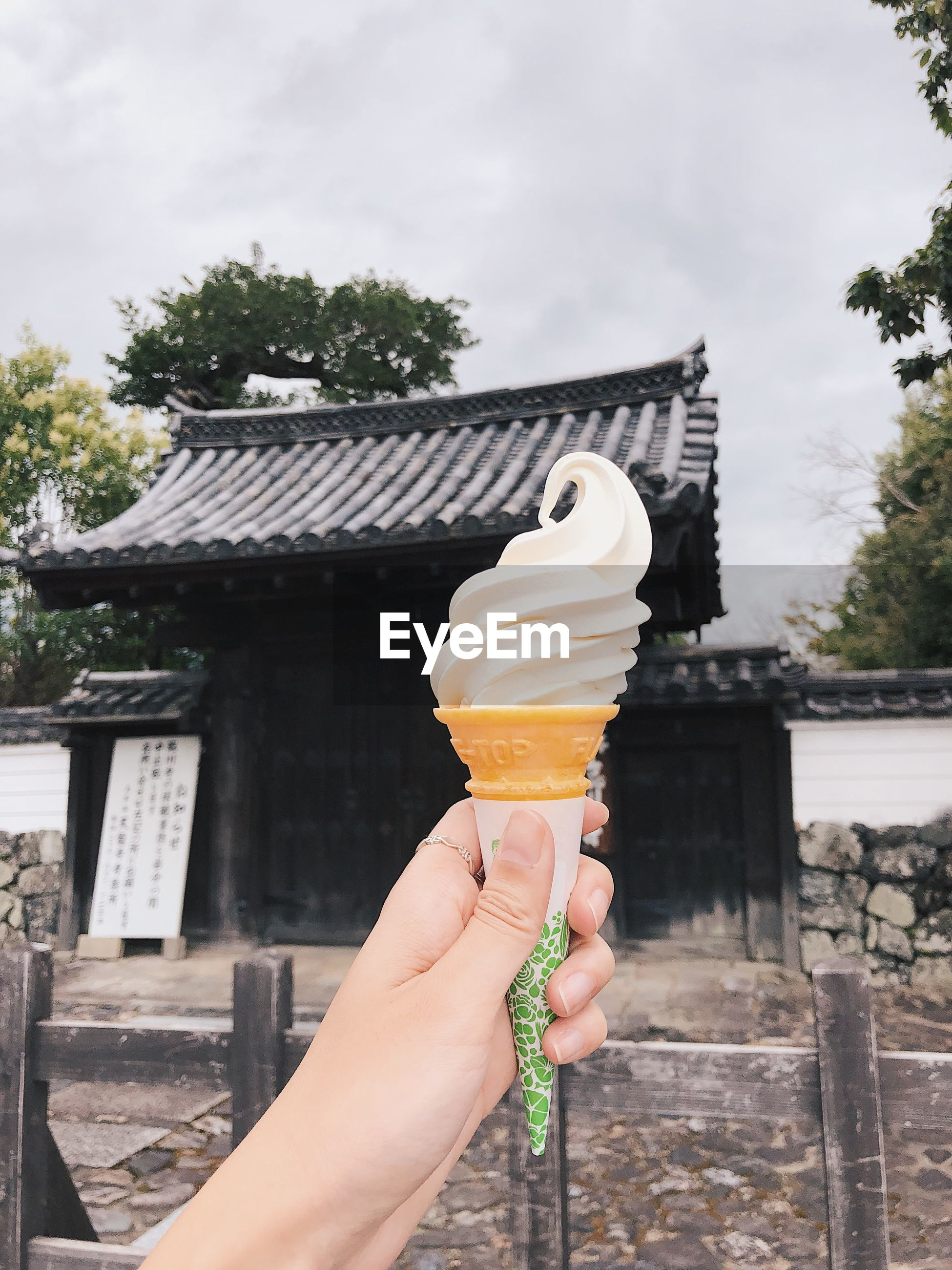 Cropped hand holding ice cream cone against house