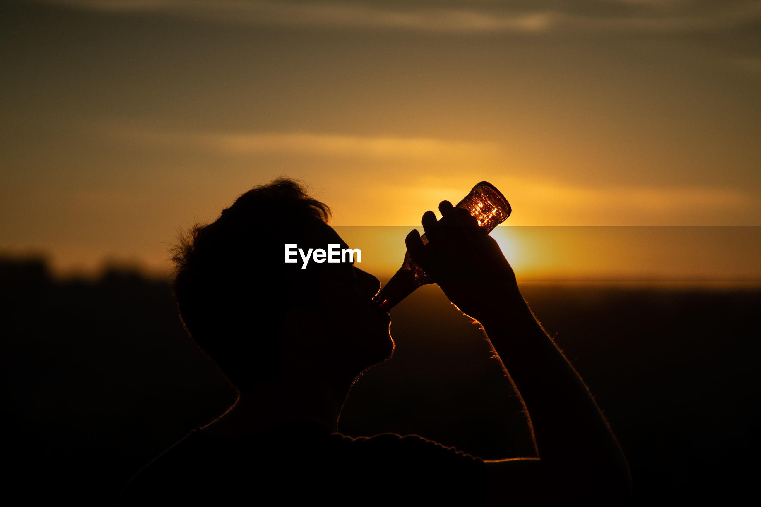 Silhouette man drinking beer against orange sky