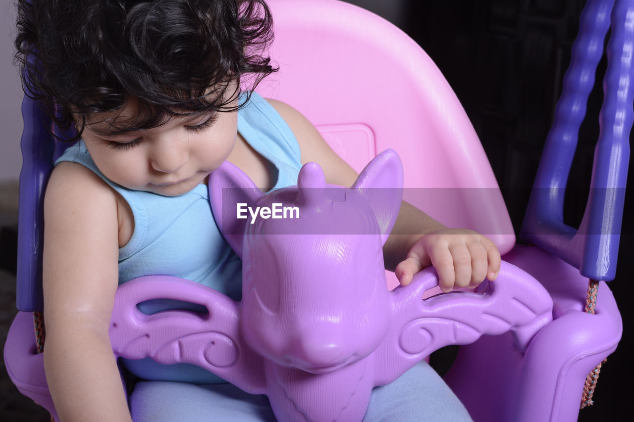 childhood, child, real people, pink color, savings, one person, front view, investment, piggy bank, baby, girls, indoors, lifestyles, sitting, innocence, young, purple, coin bank