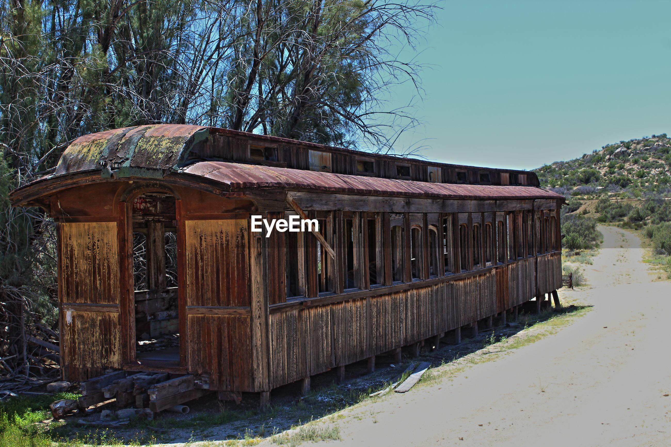 Abandoned wooden railroad car by empty road against clear sky