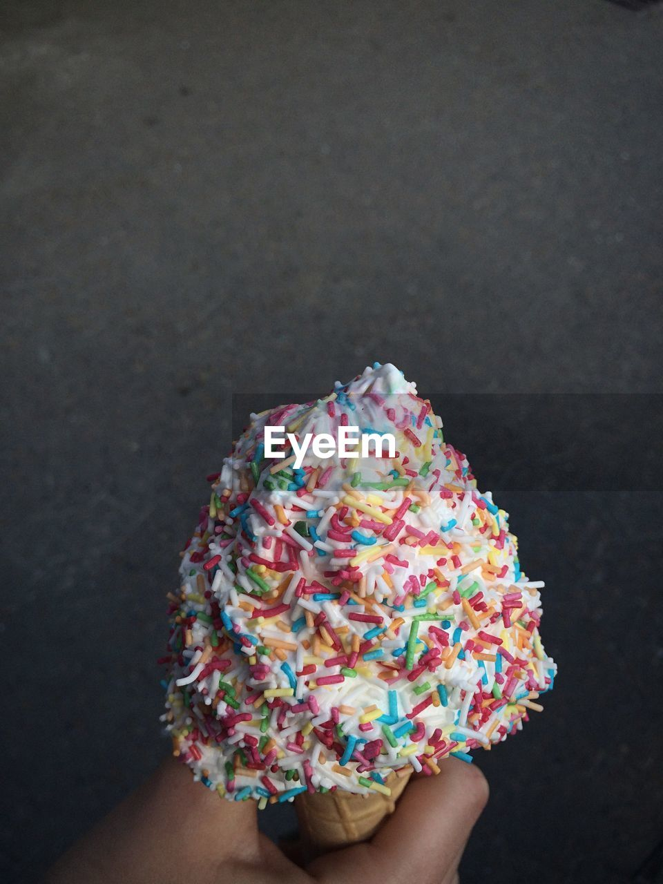 Close-Up Of Hand Holding Ice Cream Cone Against Black Background