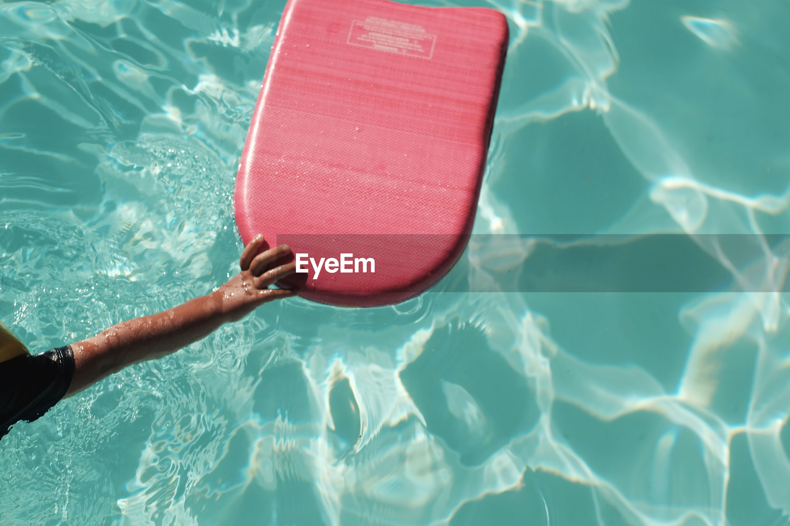 Cropped hand of child holding pool raft in swimming pool on sunny day