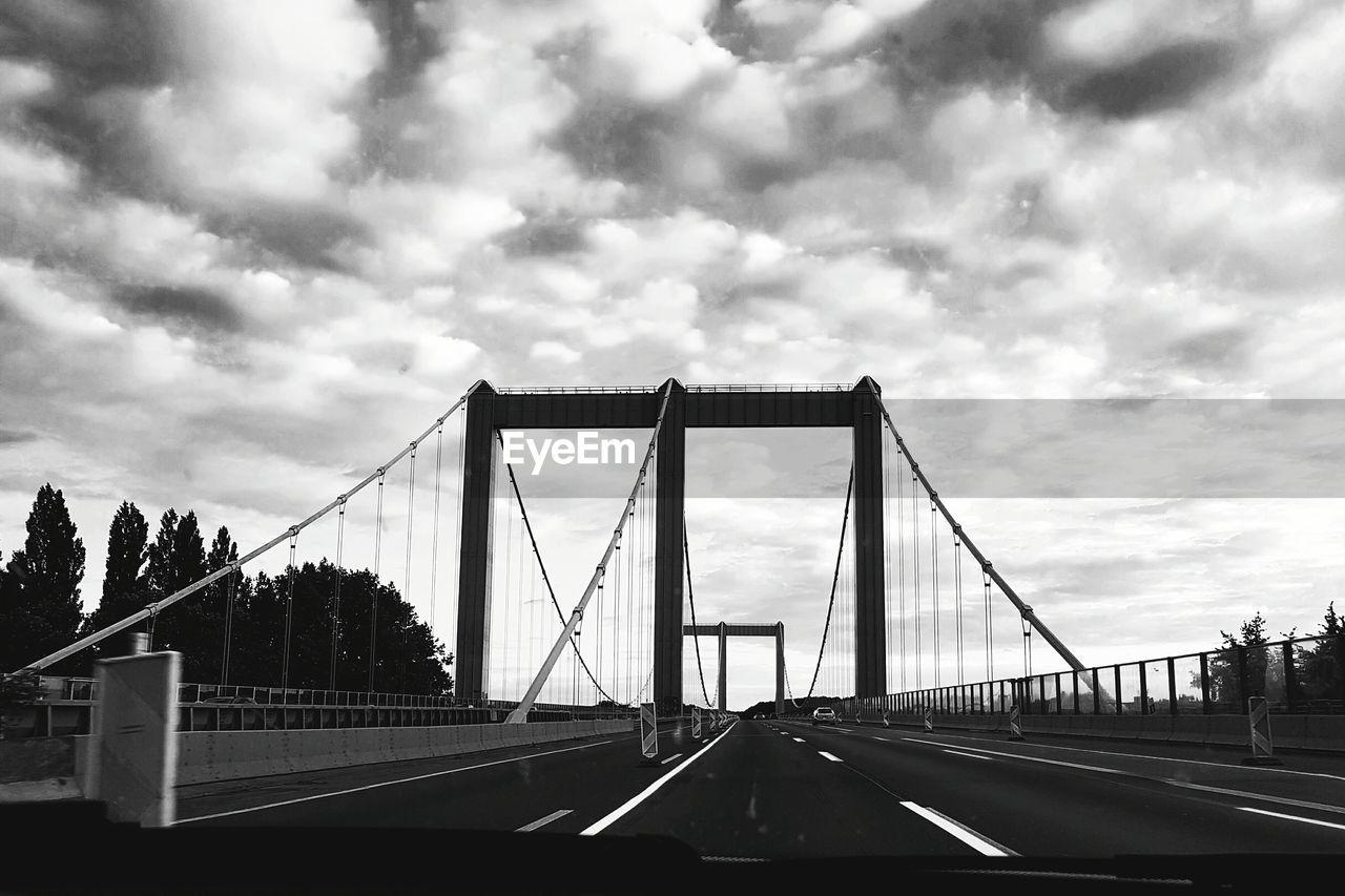 bridge - man made structure, connection, suspension bridge, sky, cloud - sky, transportation, architecture, the way forward, built structure, outdoors, travel destinations, railing, travel, day, bridge, road, no people, tree, city, chain bridge