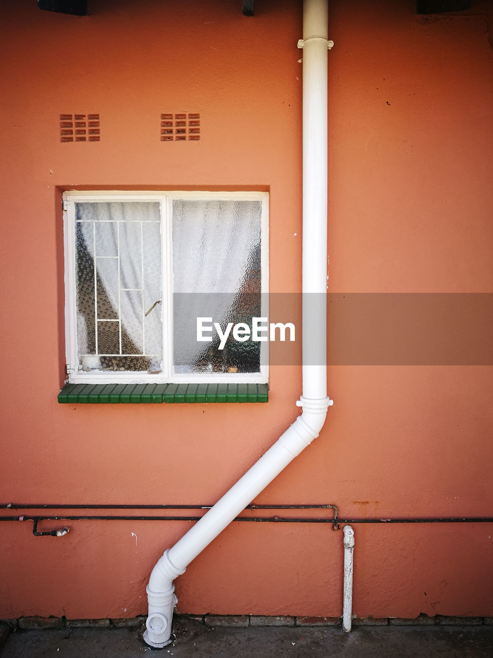 Low angle view of pipe by window on building
