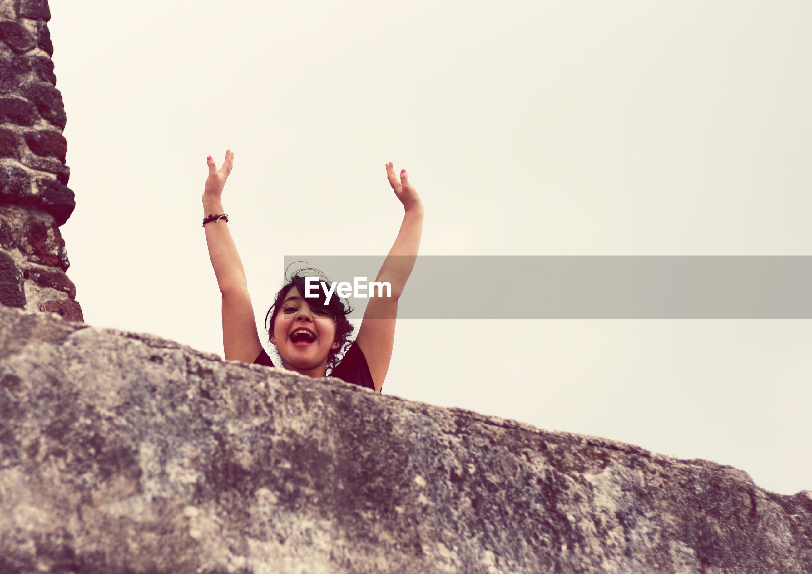 Portrait of smiling woman with arms raised by wall against clear sky