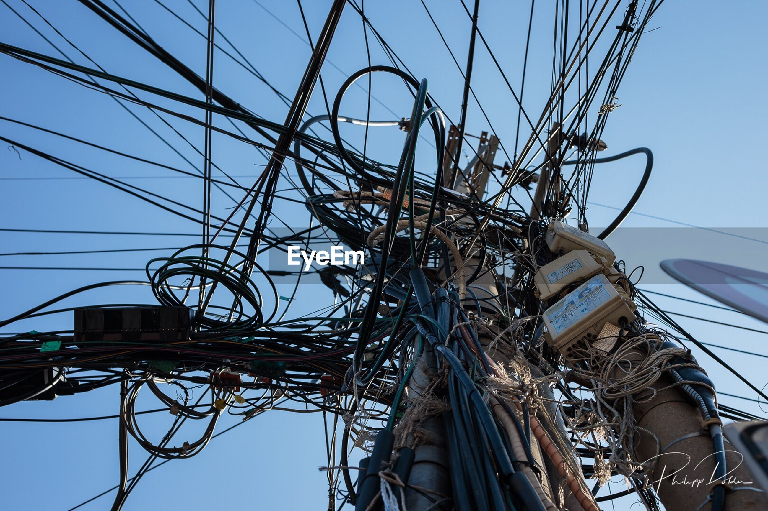 cable, power supply, technology, power line, connection, complexity, low angle view, electricity, day, tangled, fuel and power generation, no people, outdoors, electricity pylon, telephone line, sky