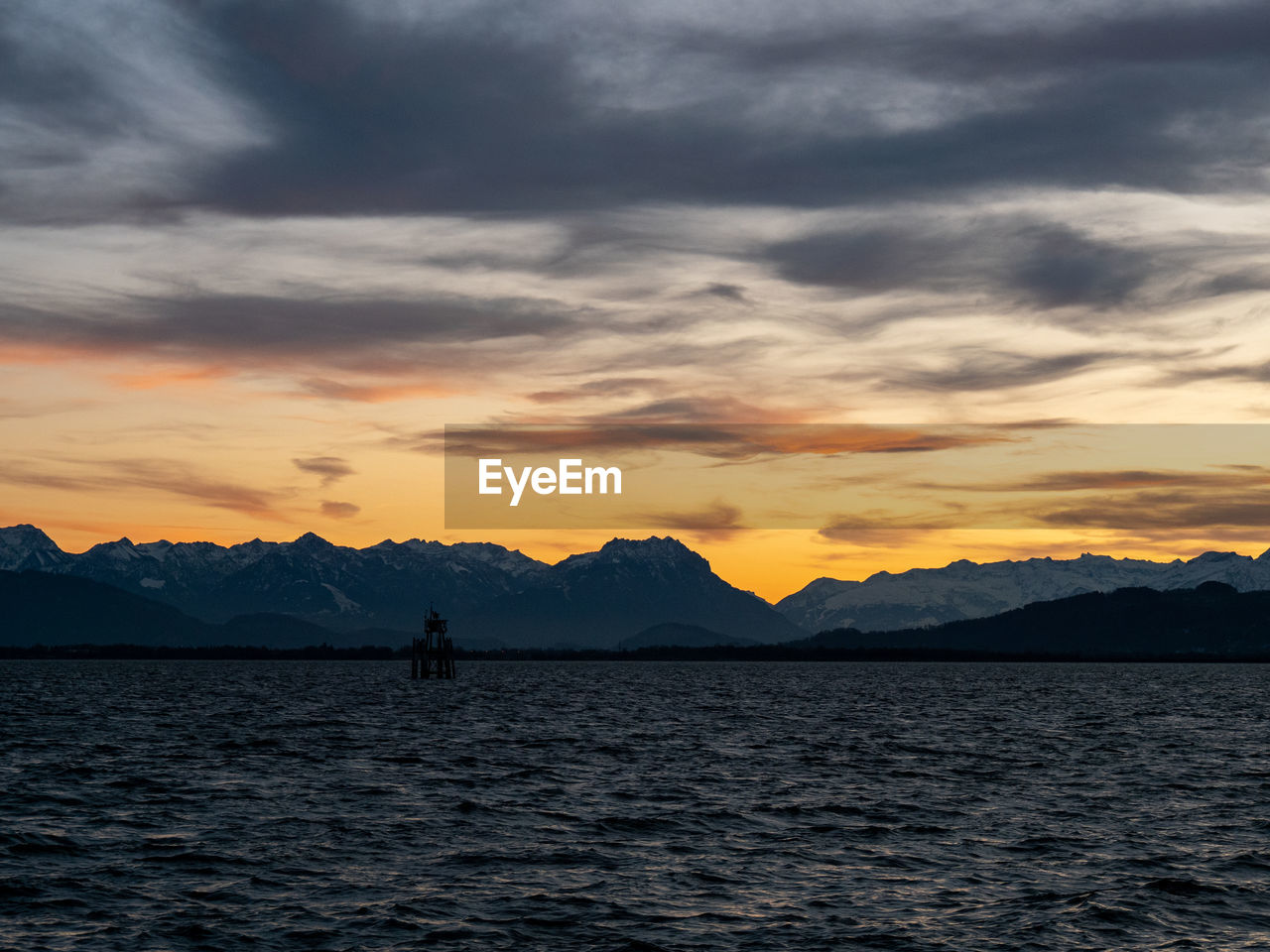 sunset, sky, cloud - sky, beauty in nature, scenics - nature, mountain, silhouette, tranquility, tranquil scene, water, real people, waterfront, orange color, nature, idyllic, non-urban scene, standing, one person, leisure activity, mountain range, outdoors