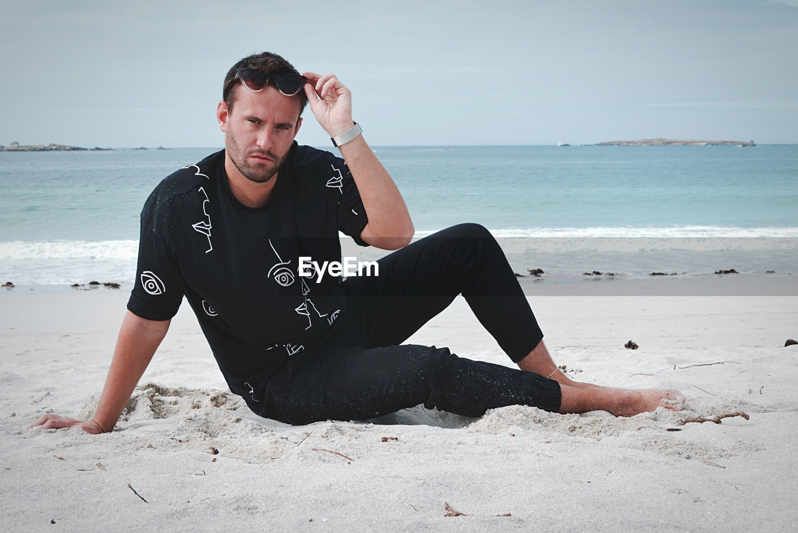 YOUNG MAN SITTING ON BEACH AGAINST SEA