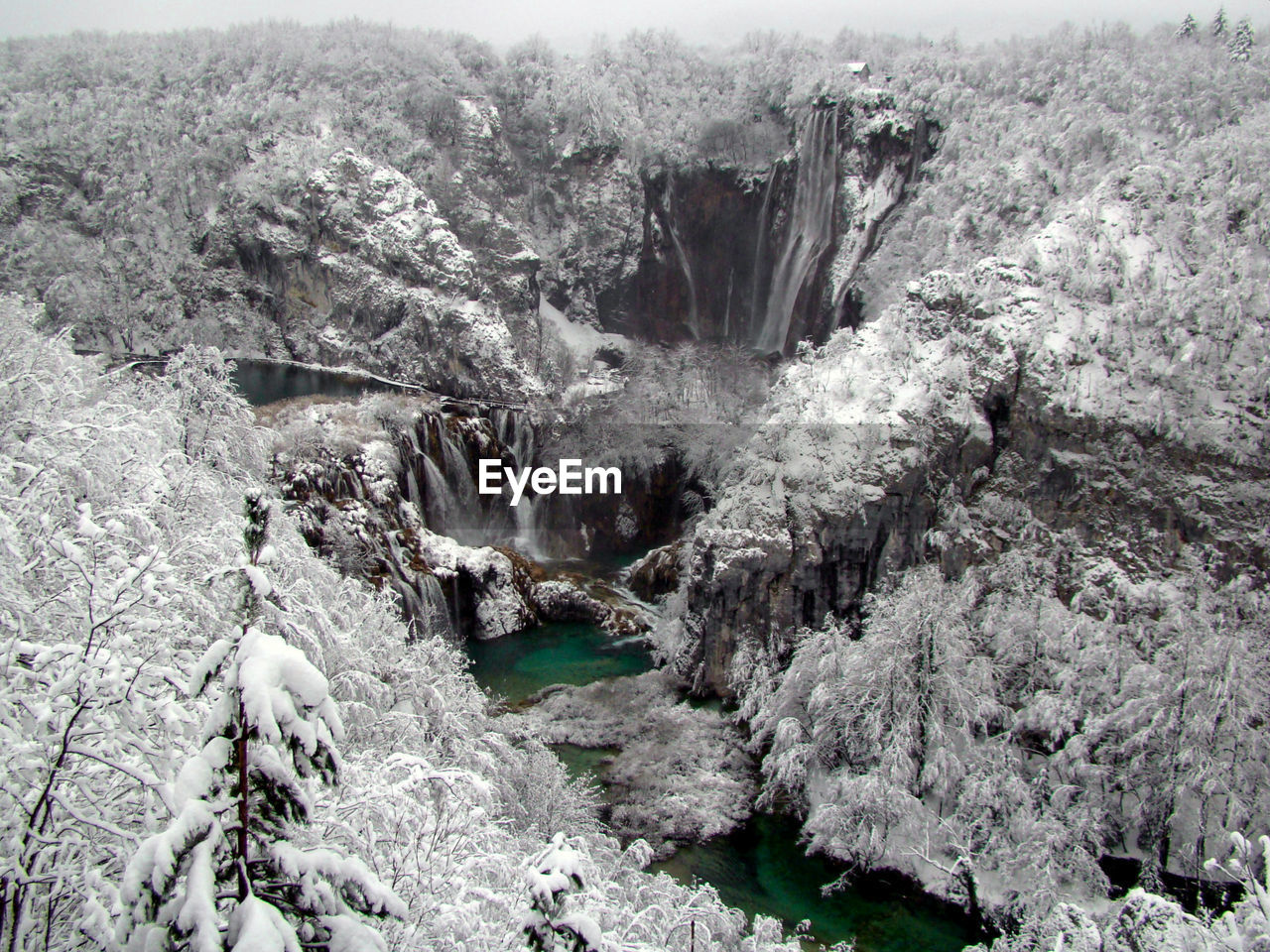 High angle view of frozen waterfall amidst trees in forest