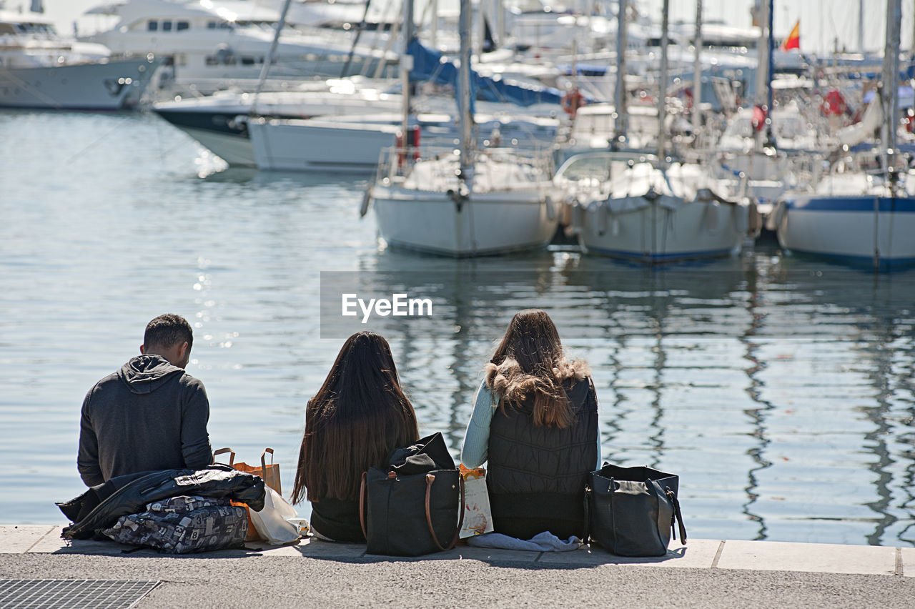 Rear View Of People Sitting At Harbor