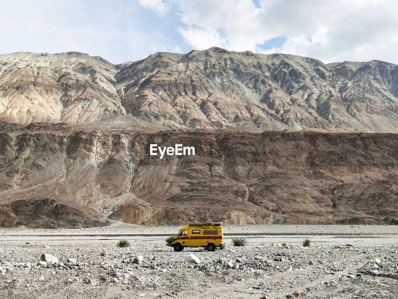 Yellow Off-Road Vehicle On Field Against Mountains Against Sky