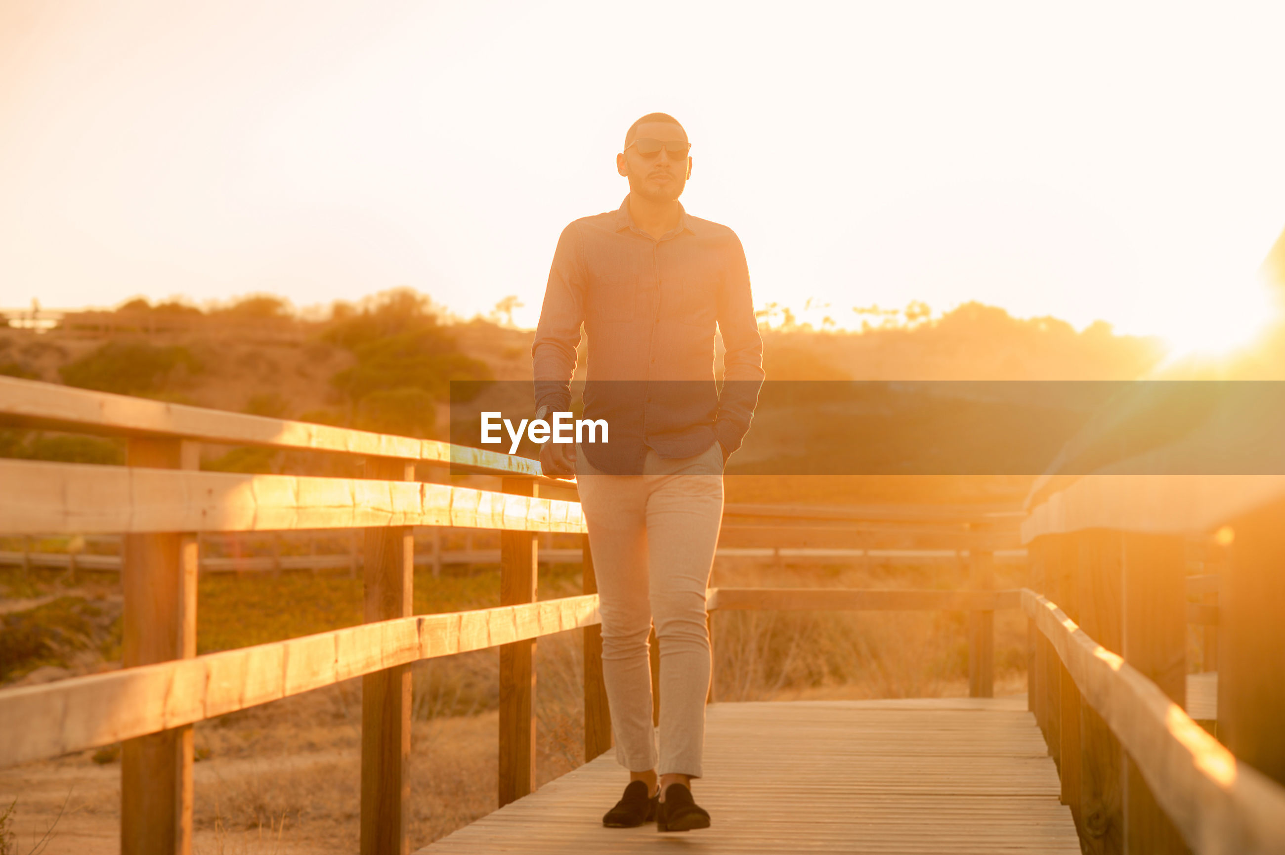 Full length of man standing by railing during sunset