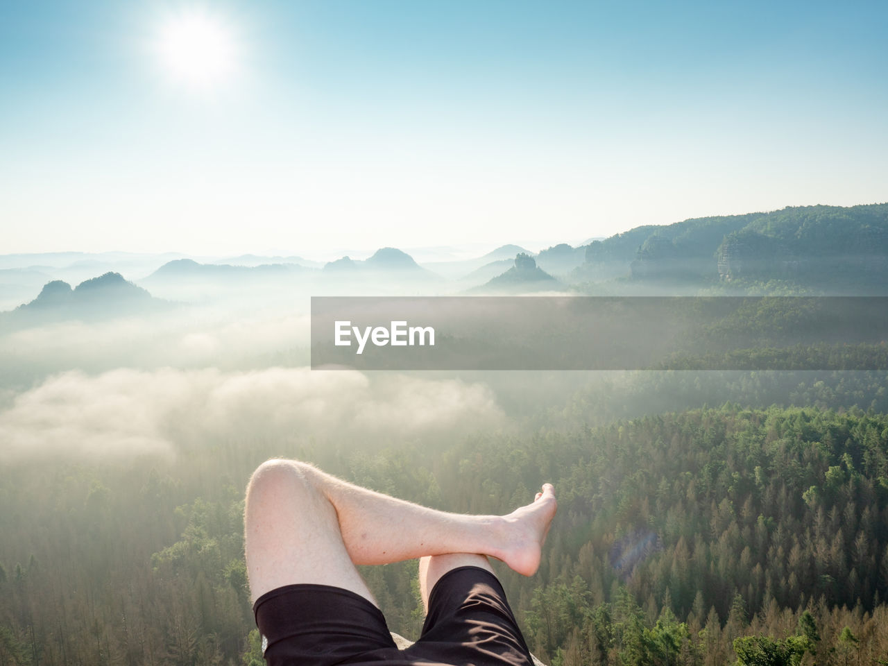 First person view to resting hiking legs,resting during hike. high rocks, clear sky and sun,