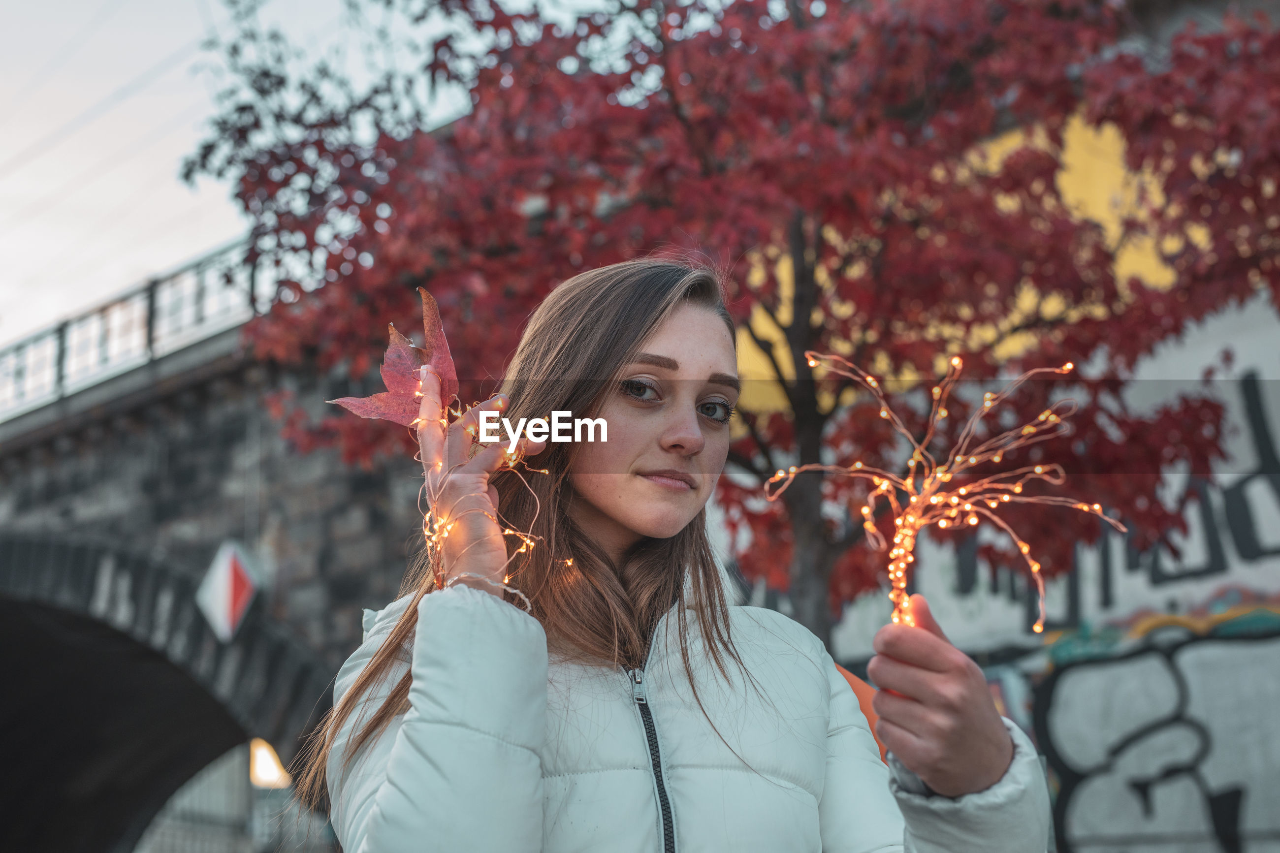 Portrait of young woman holding illuminated lighting equipment against tree during autumn