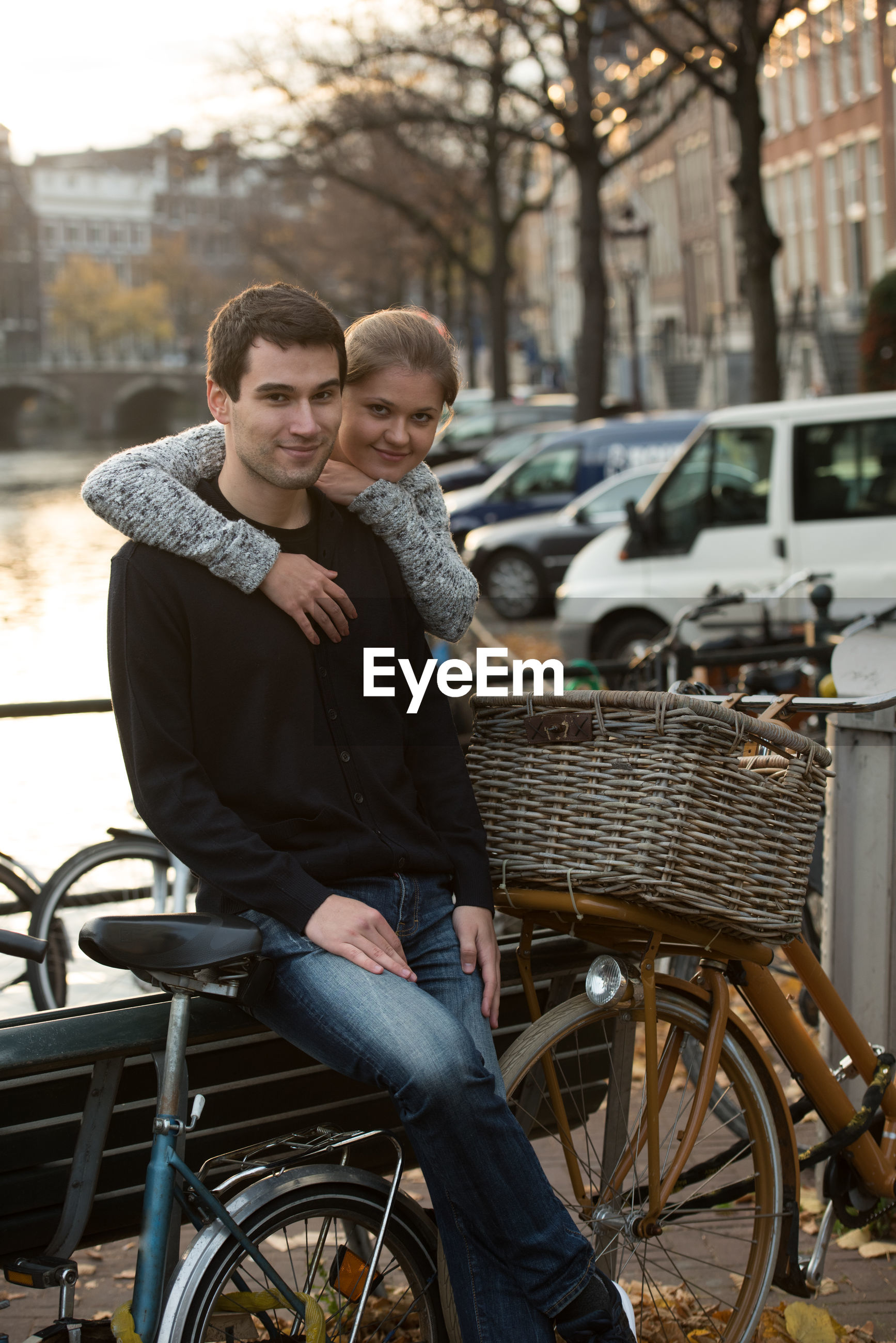 Young couple with bicycle by railing in city