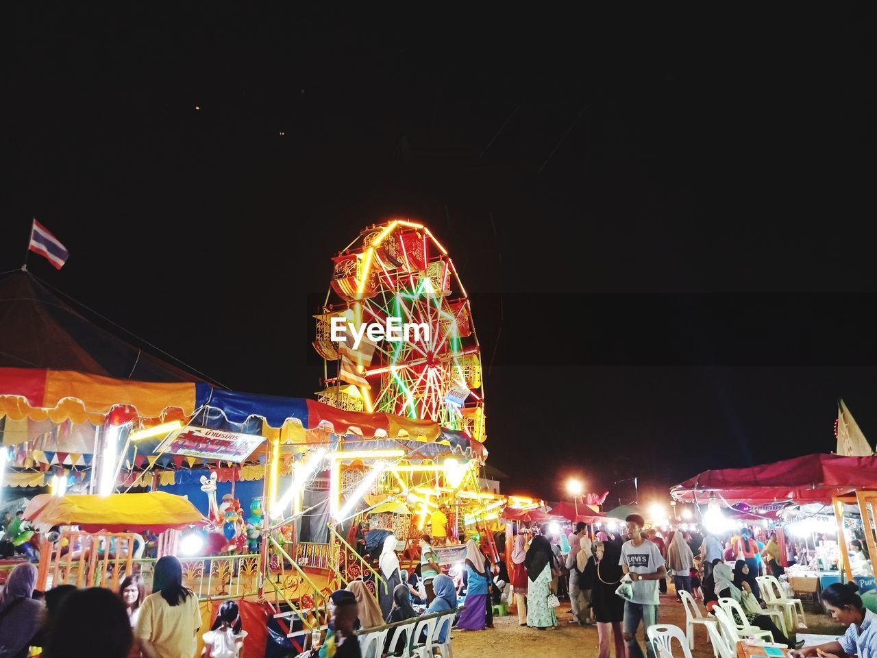 night, group of people, illuminated, crowd, amusement park, real people, amusement park ride, arts culture and entertainment, large group of people, sky, built structure, leisure activity, lifestyles, architecture, men, women, enjoyment, copy space, city, outdoors, festival, light, excitement