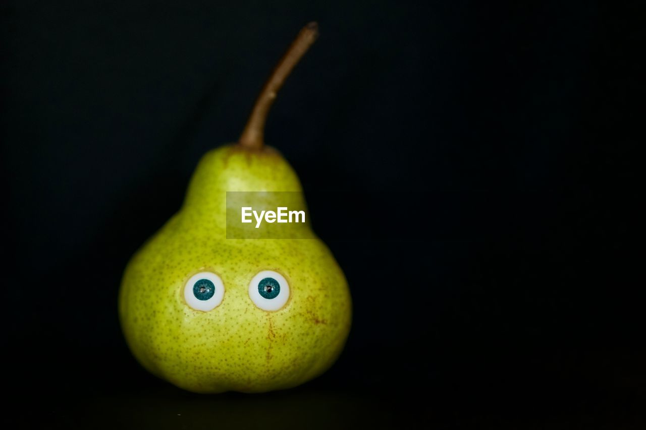 Close-up of pear against black background