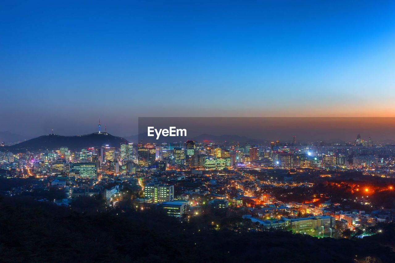 Aerial view of illuminated cityscape against blue sky at night