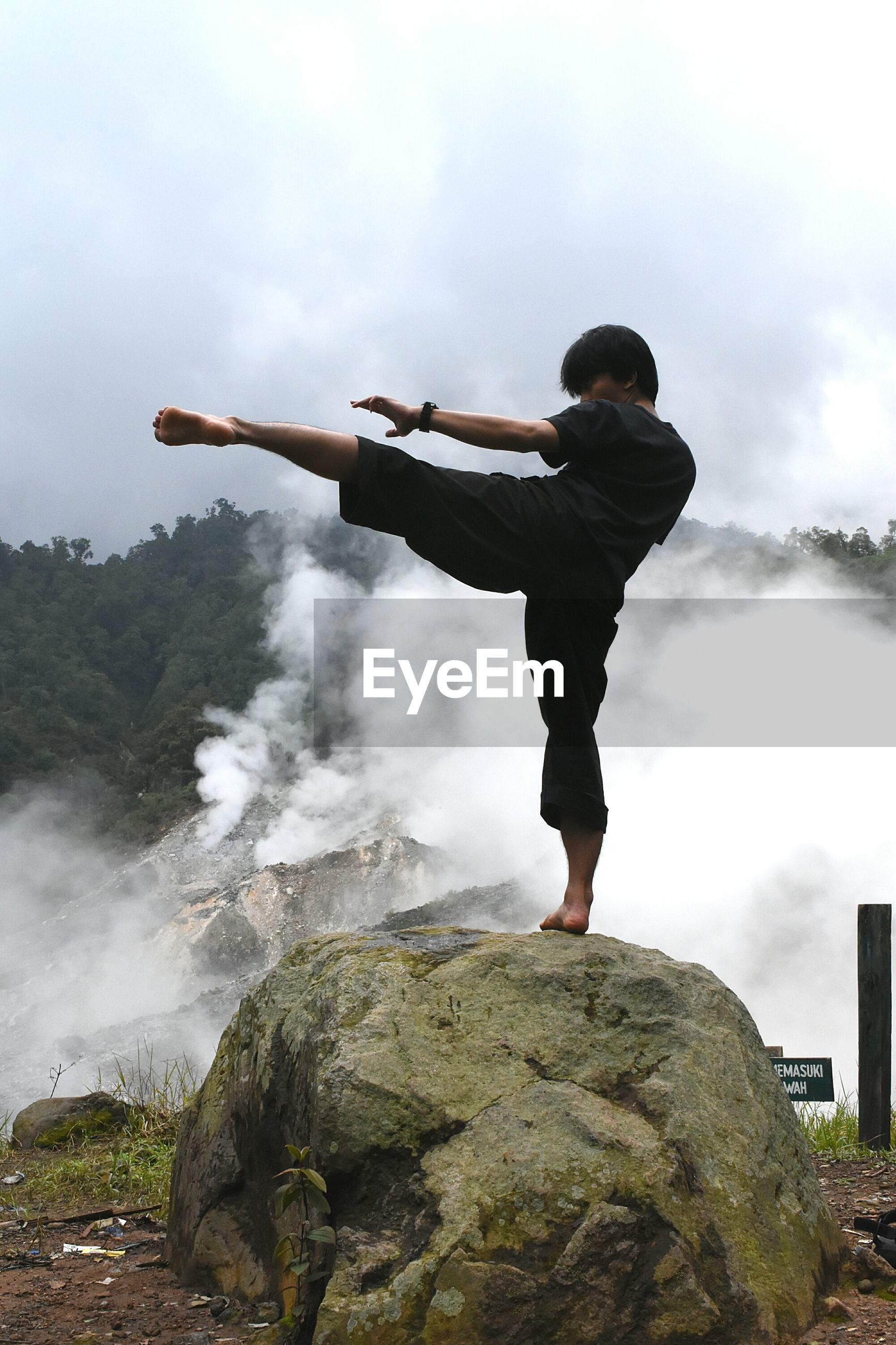Full length of man kicking while standing on rock against sky