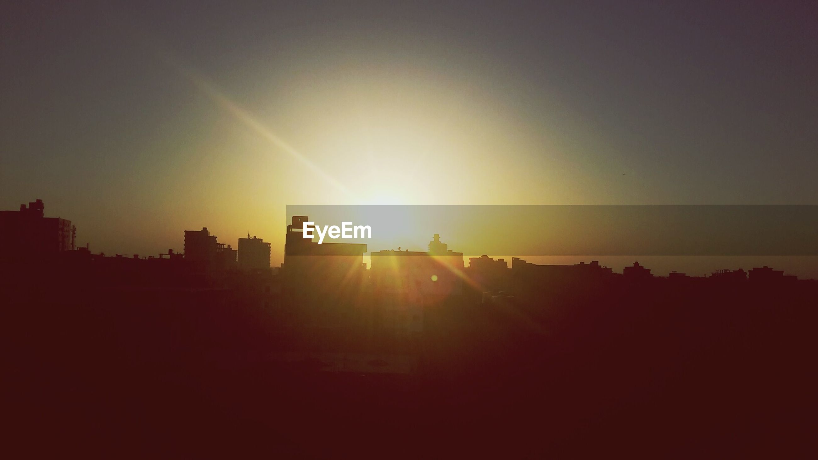 sunset, sun, silhouette, building exterior, built structure, architecture, sunlight, sunbeam, copy space, orange color, lens flare, sky, clear sky, city, outdoors, nature, beauty in nature, building, no people, dark