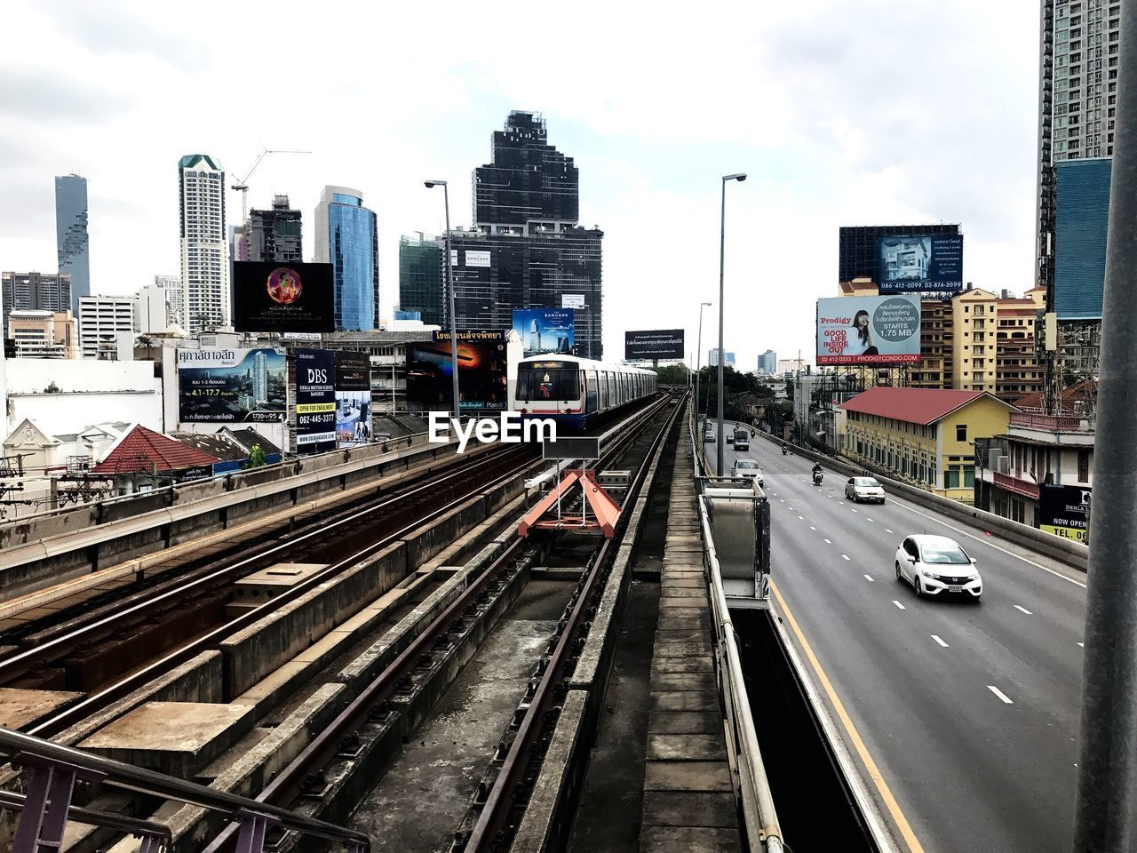 transportation, building exterior, architecture, built structure, city, road, skyscraper, traffic, tower, car, sky, land vehicle, railroad track, mode of transport, cityscape, outdoors, city life, travel destinations, public transportation, no people, urban skyline, tall, high street, day
