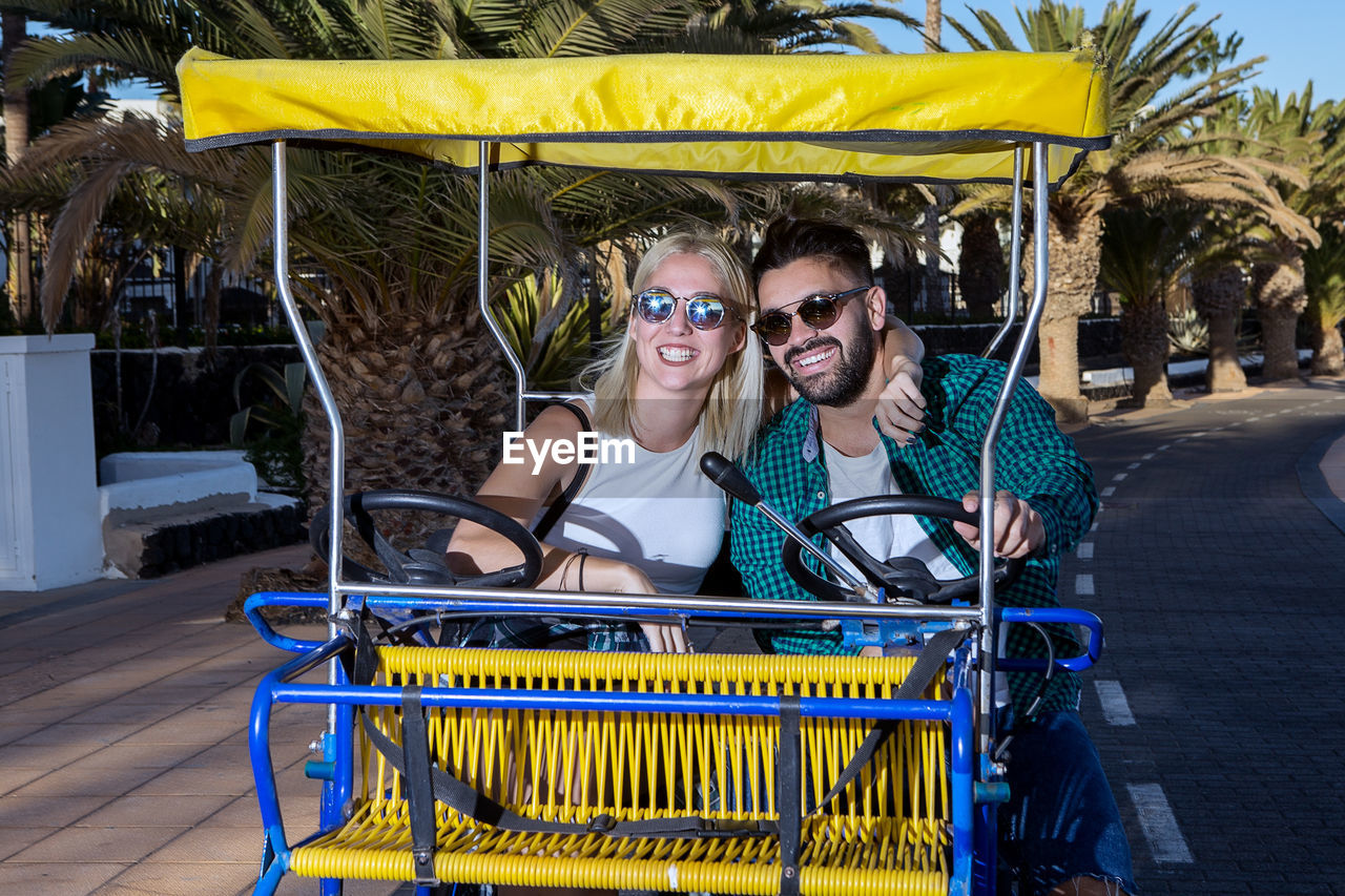 Smiling Couple Riding Cart Cycle Outdoors