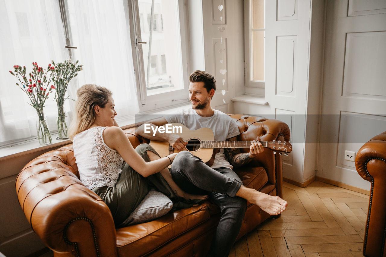 Man Looking At Woman While Playing Guitar On Sofa