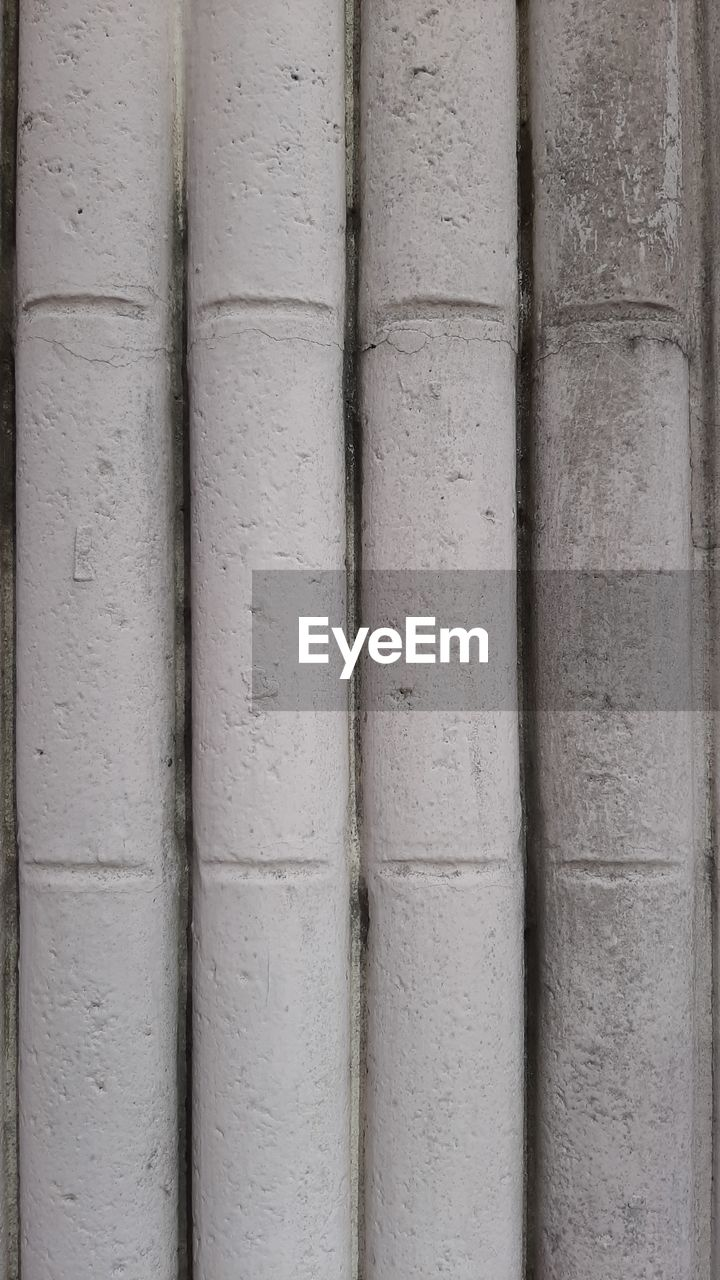 backgrounds, full frame, no people, pattern, architecture, close-up, side by side, textured, built structure, day, in a row, wood - material, outdoors, repetition, wall - building feature, group of objects, large group of objects, gray, order, abundance, concrete, corrugated
