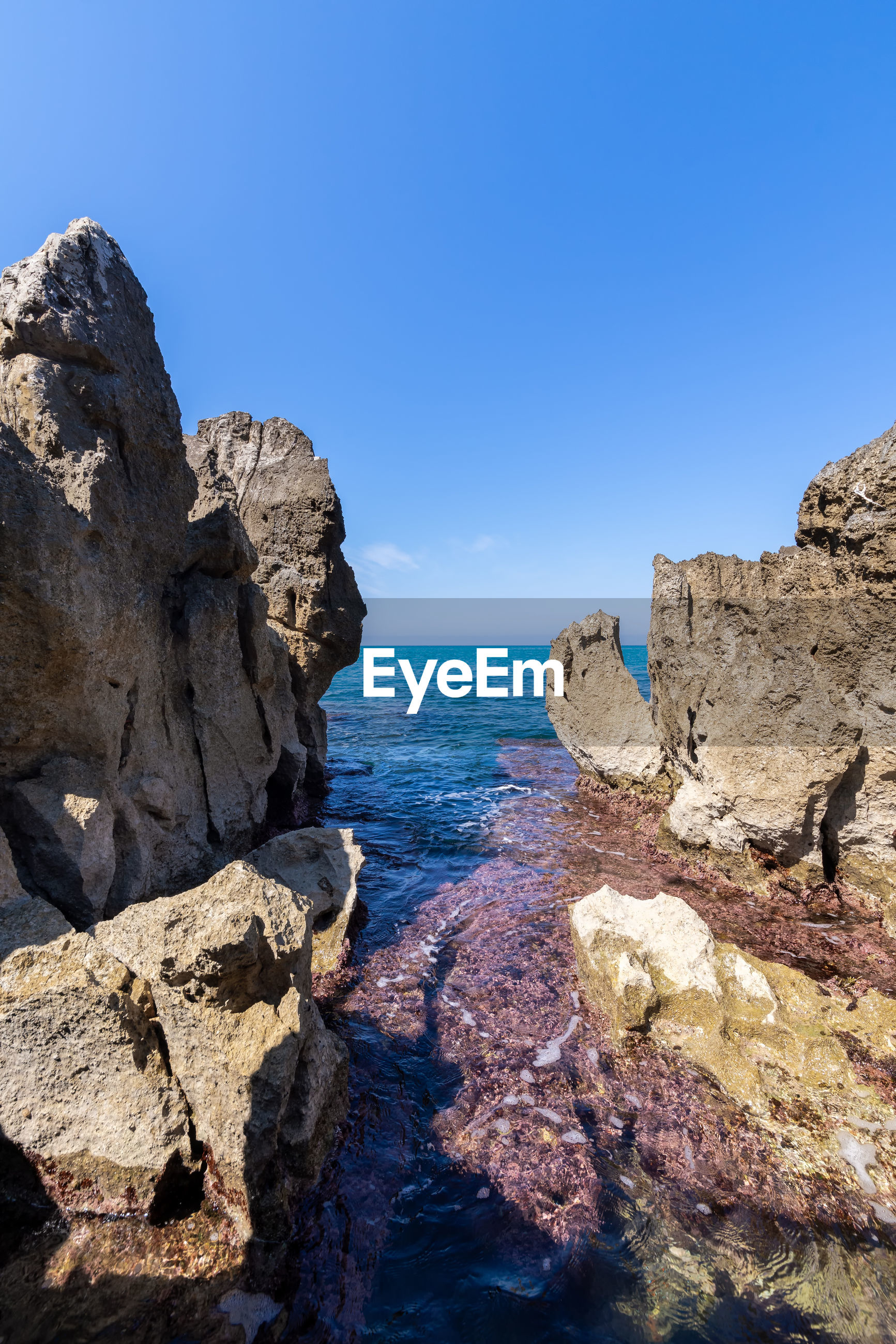 ROCK FORMATION ON SEA AGAINST CLEAR BLUE SKY