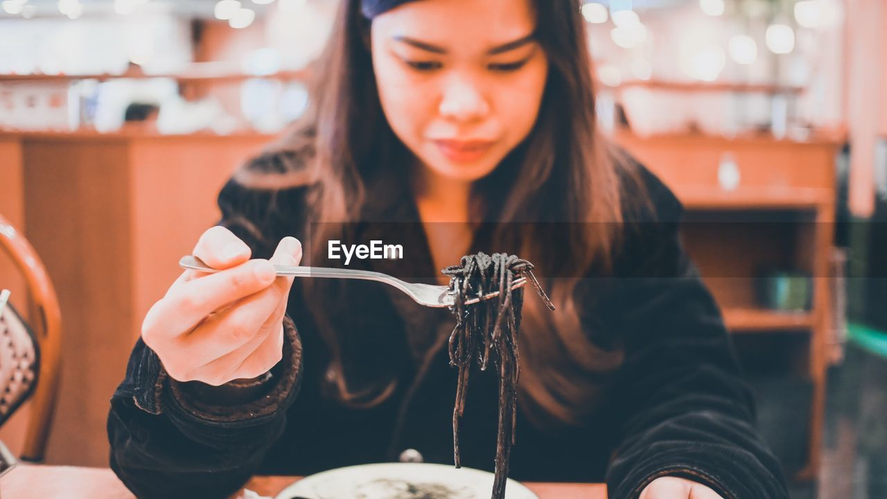 Midsection Of Woman Holding Noodles In Restaurant