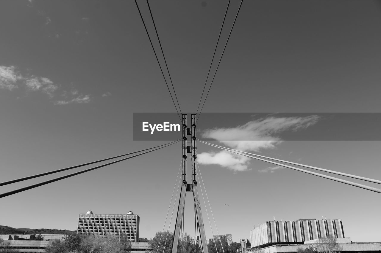 sky, built structure, architecture, low angle view, building exterior, cable, nature, cloud - sky, connection, no people, city, day, electricity, transportation, building, outdoors, bridge, bridge - man made structure, tall - high, office building exterior, skyscraper, power supply