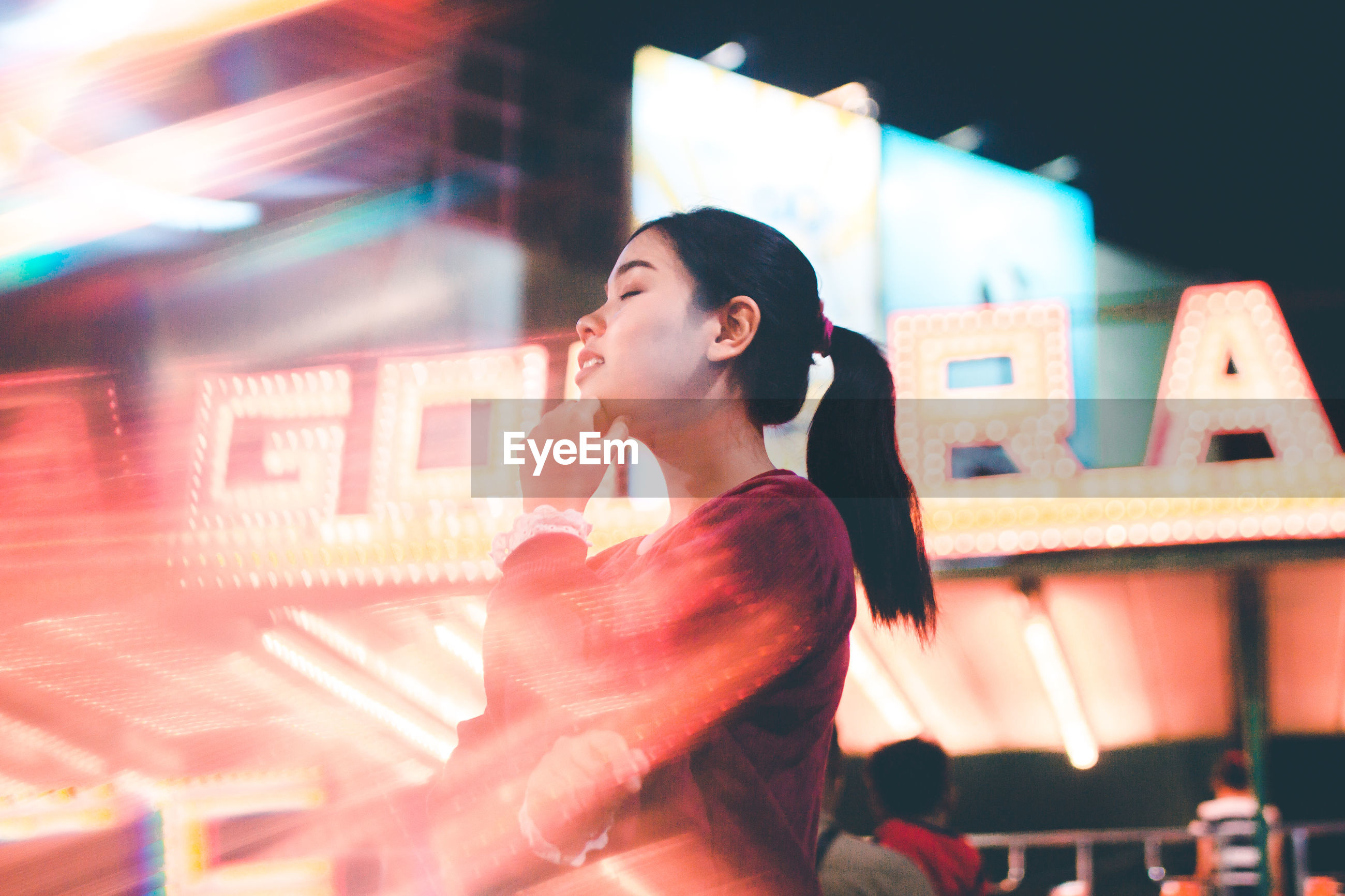 Low angle view of young woman in illuminated street at night