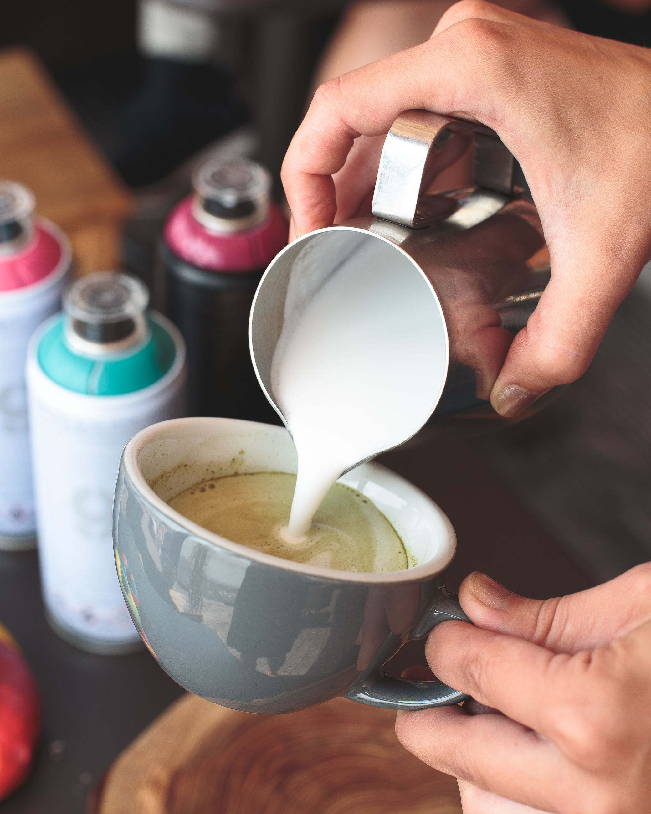 Cropped image of hand pouring milk in coffee cup