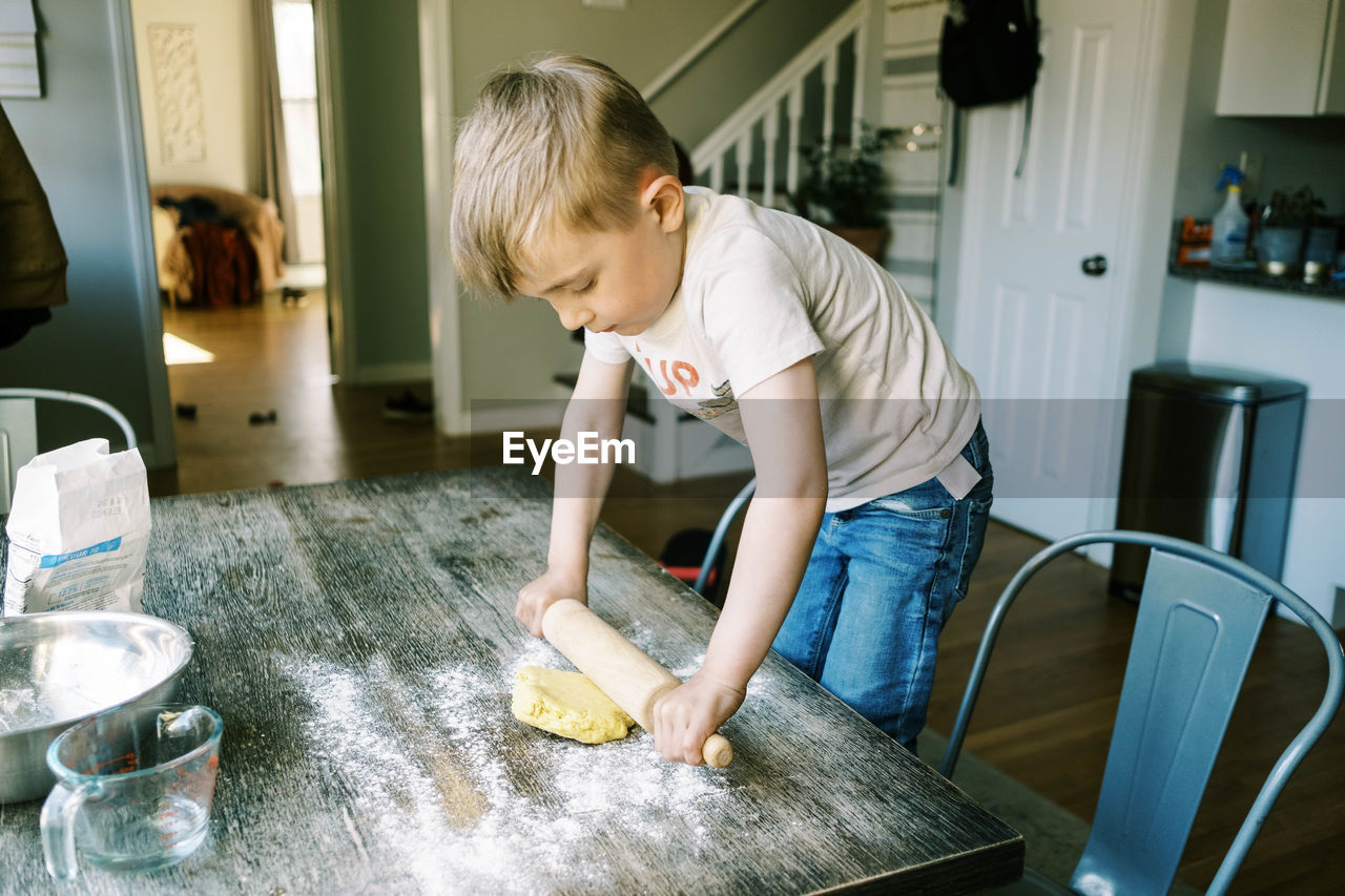 BOY STANDING IN KITCHEN AT HOME