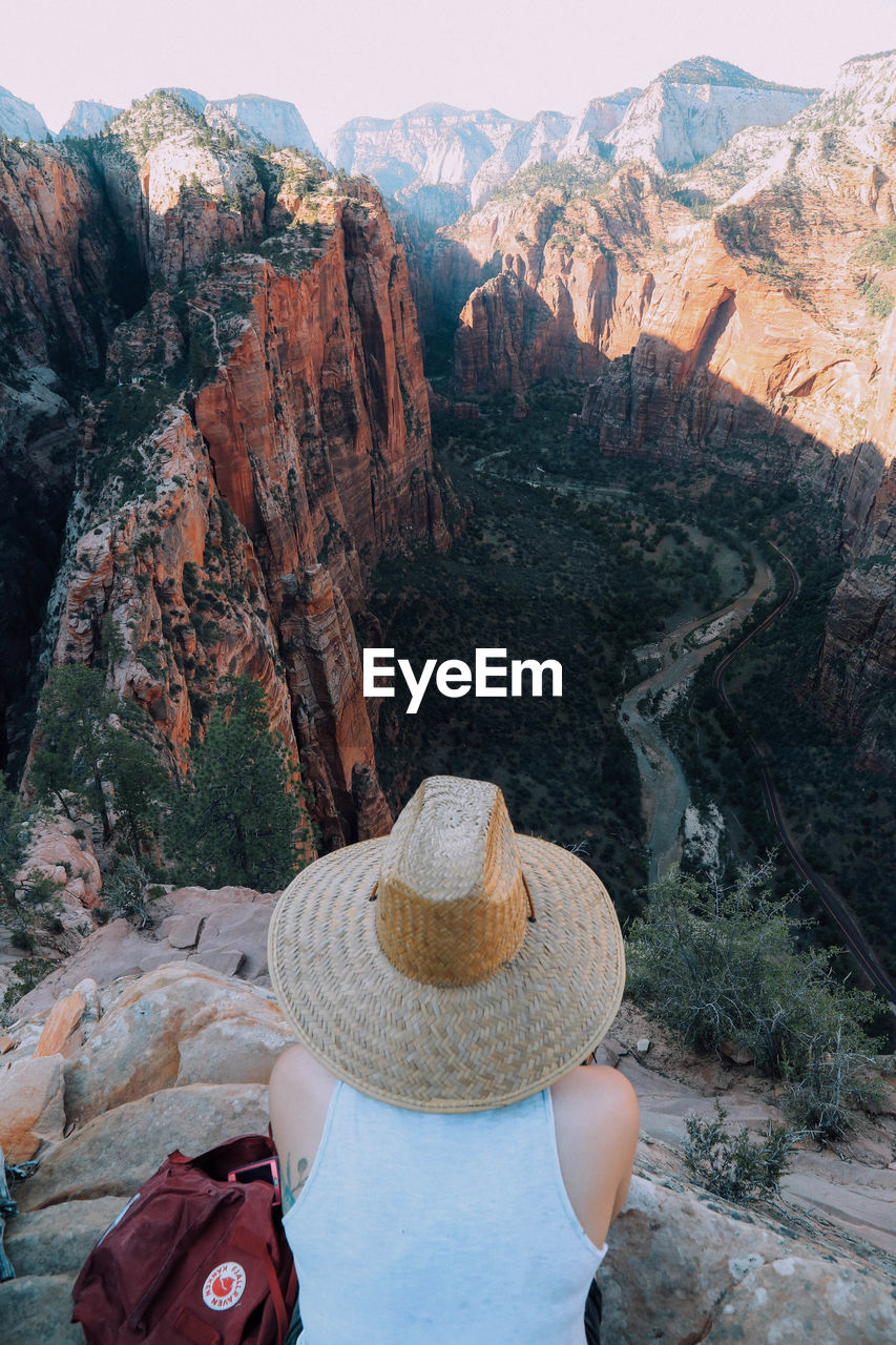 High Angle View Of Woman Sitting On Cliff At Zion National Park
