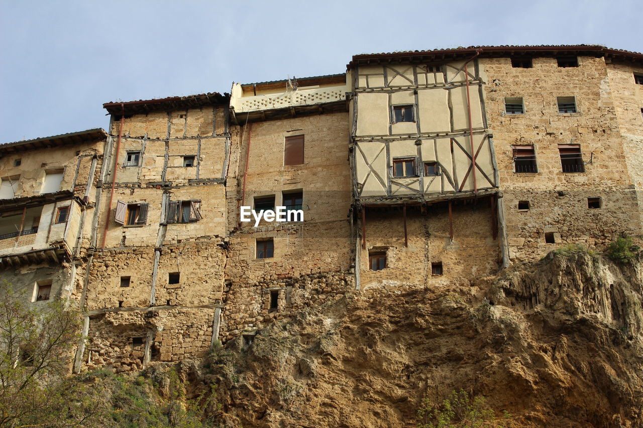 building exterior, architecture, built structure, building, sky, residential district, low angle view, window, old, history, no people, nature, the past, abandoned, house, day, outdoors, city, solid, wall, ruined, stone wall