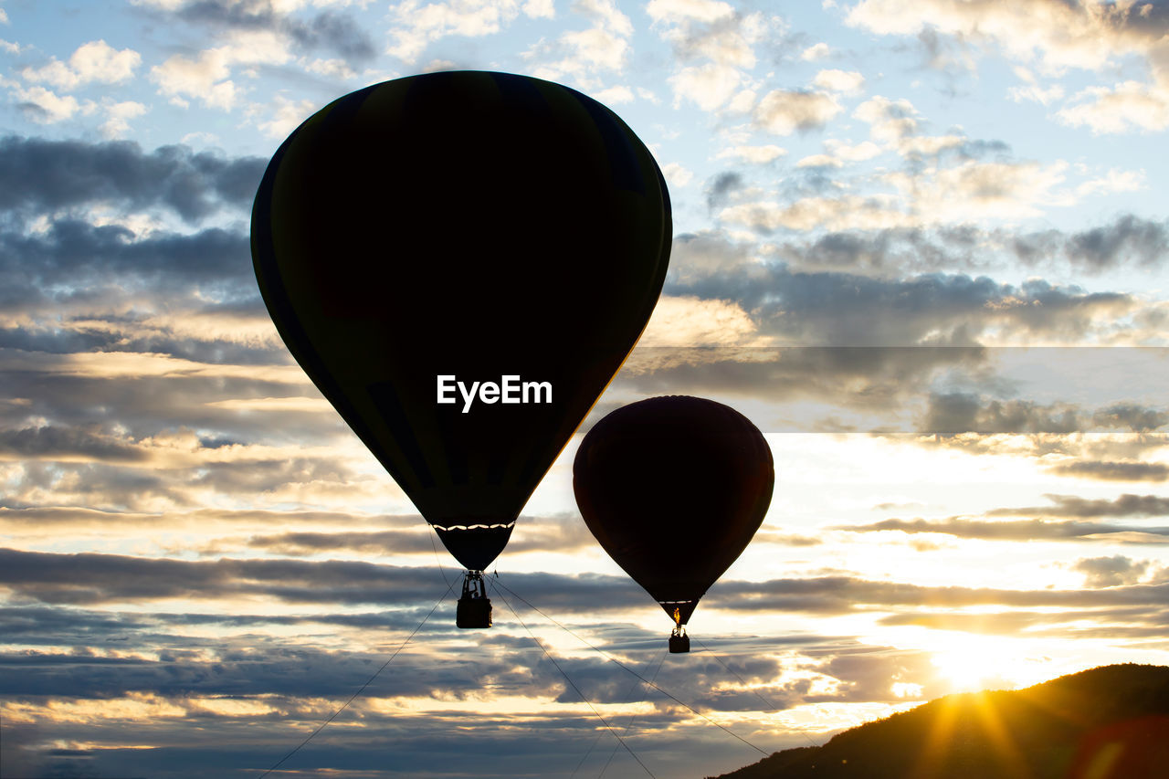 sky, cloud - sky, balloon, sunset, air vehicle, hot air balloon, transportation, flying, orange color, scenics - nature, nature, beauty in nature, mid-air, no people, silhouette, mode of transportation, outdoors, tranquility, adventure, environment, ballooning festival