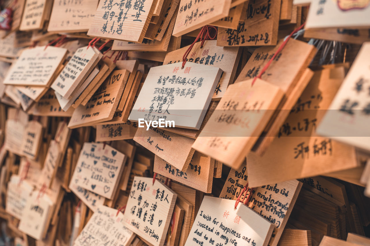 text, communication, large group of objects, no people, abundance, script, full frame, wood - material, non-western script, backgrounds, selective focus, indoors, paper, still life, note, close-up, collection, western script, high angle view, day, message