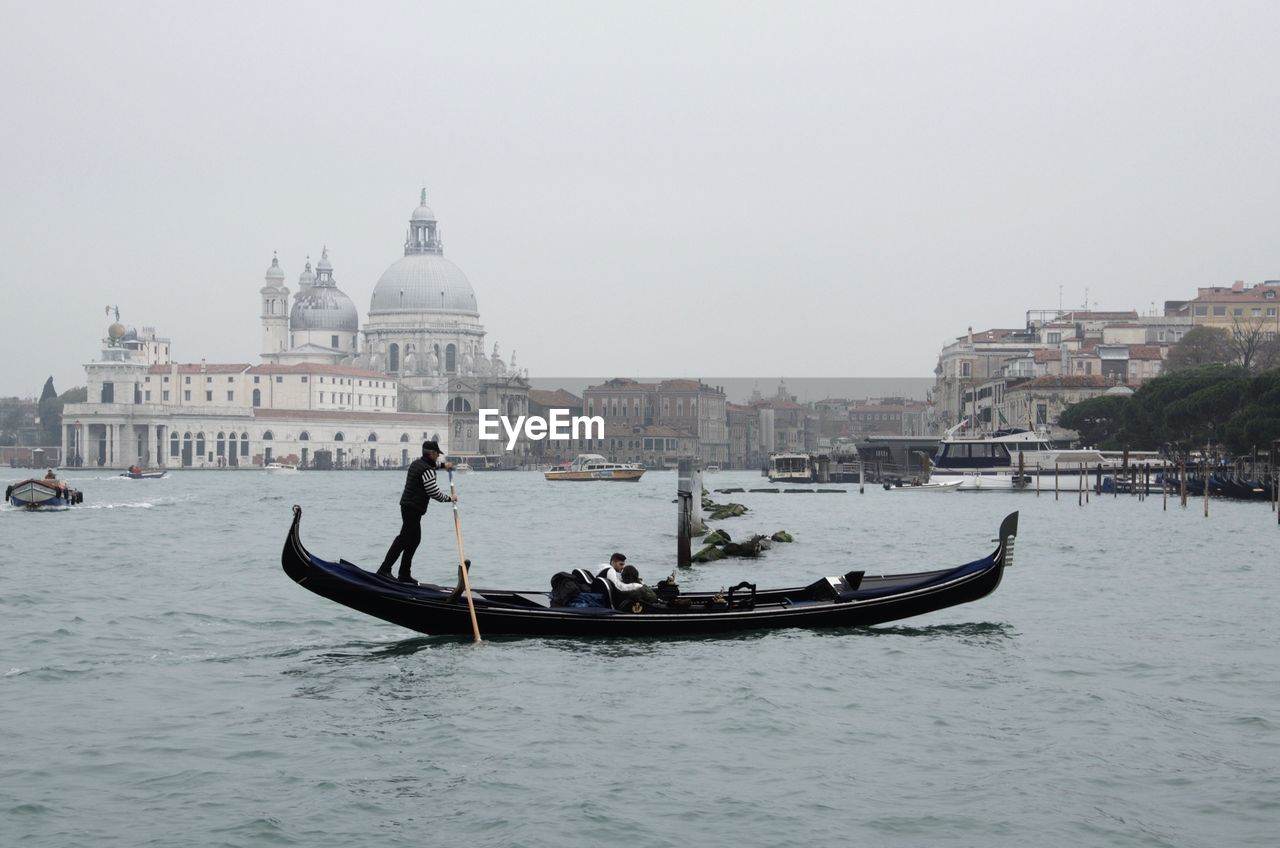 Scenic View Of A Gondola Against Venice Cityscape