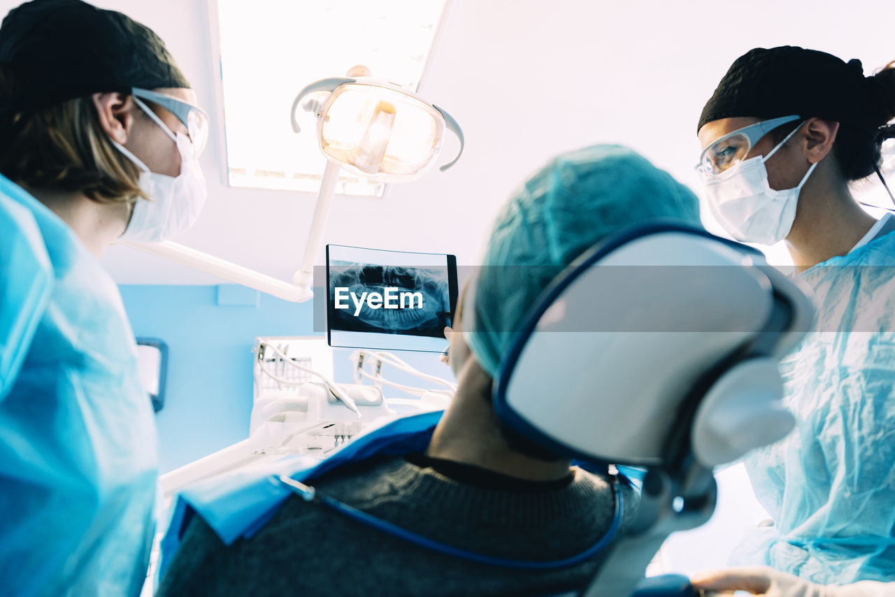 Dentists examining patient in clinic