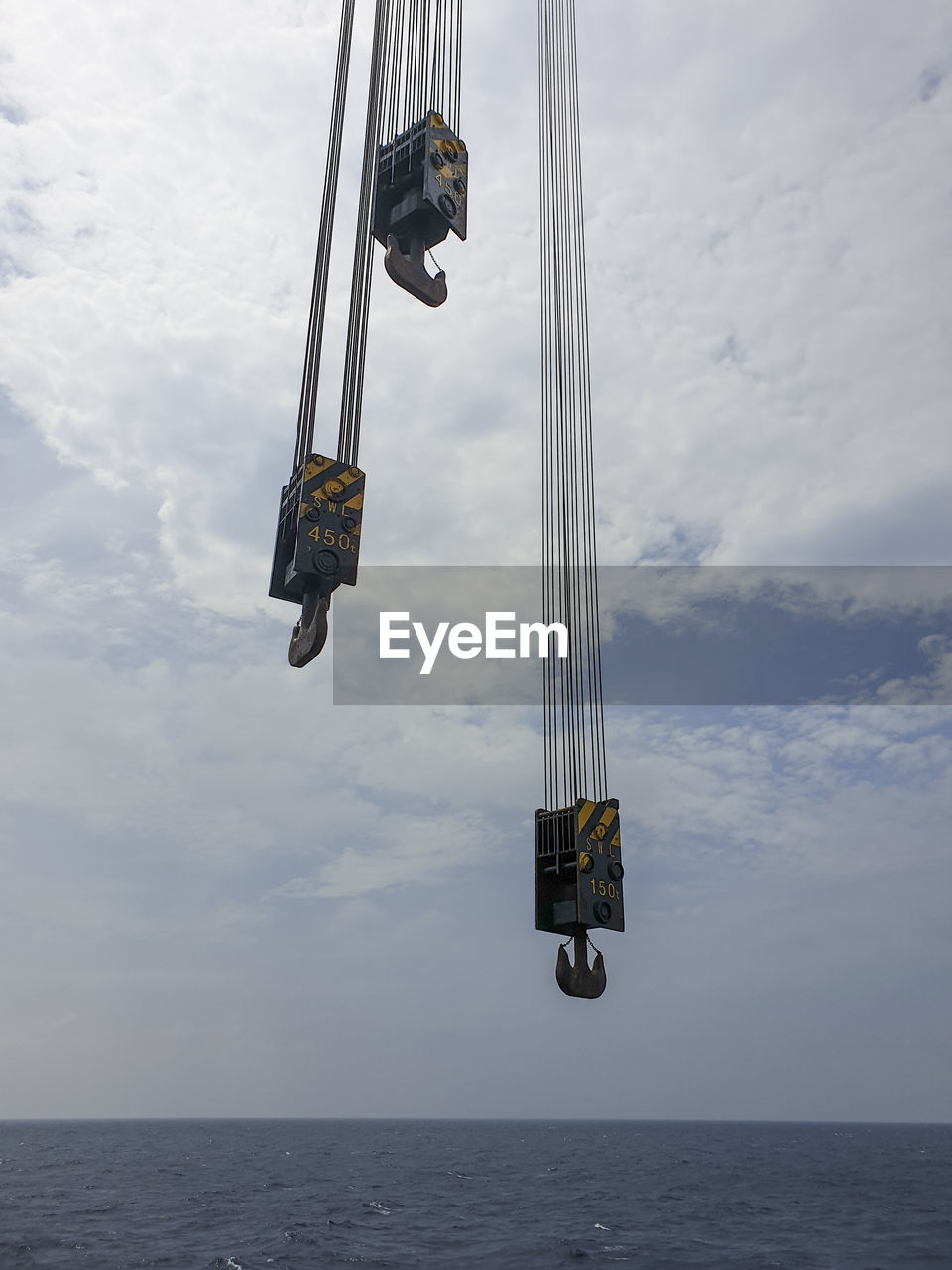 Low angle view of crane at sea against sky