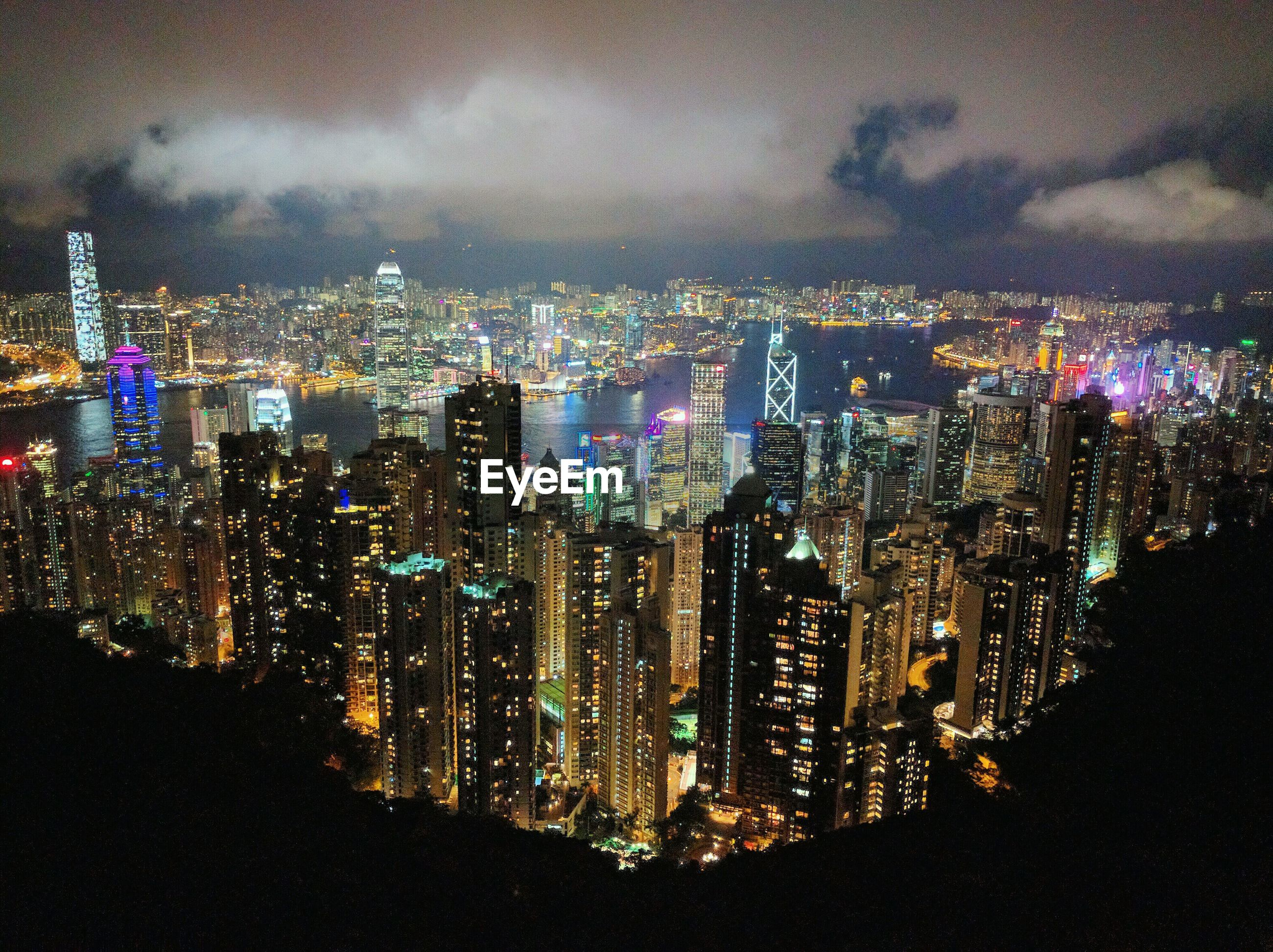 Aerial view of illuminated buildings against cloudy sky in city seen through victoria peak