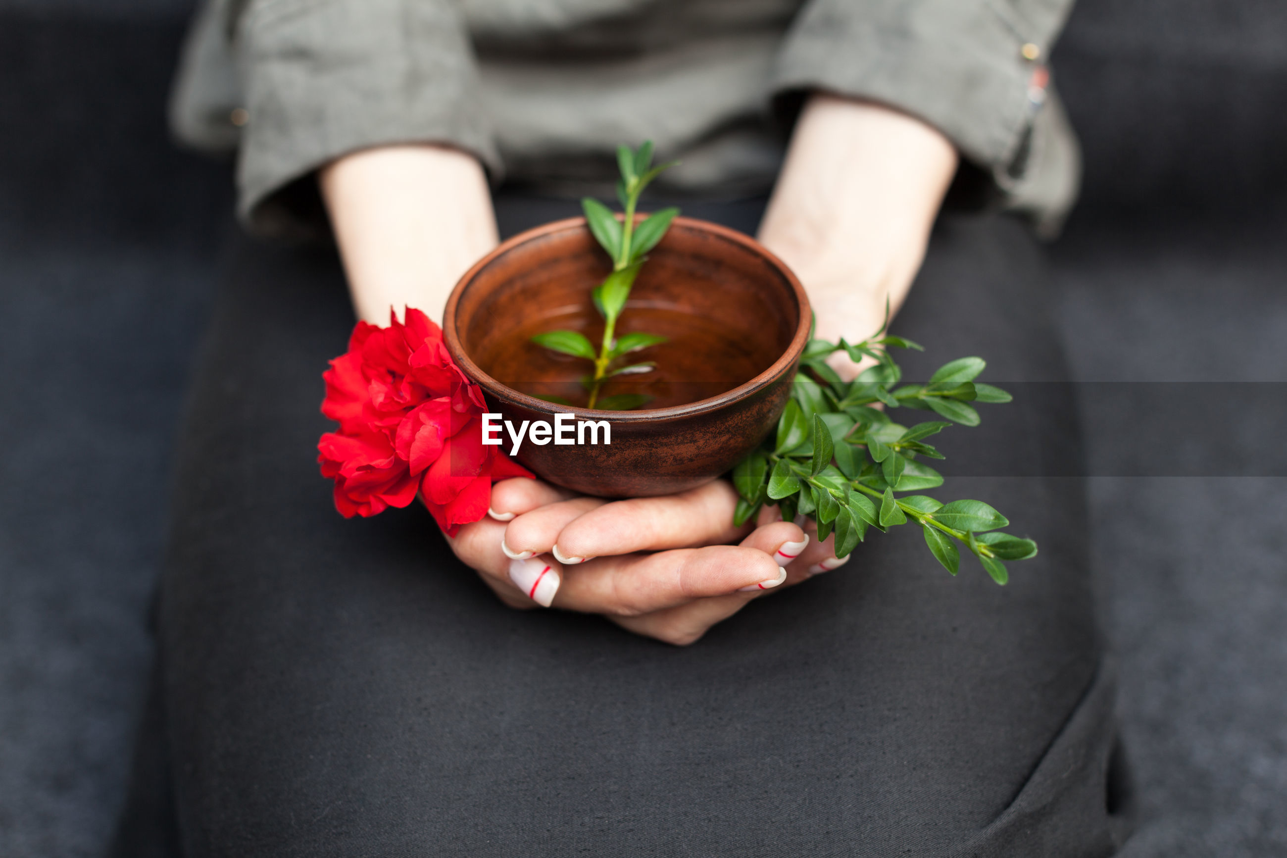 Midsection of woman holding herbal tea