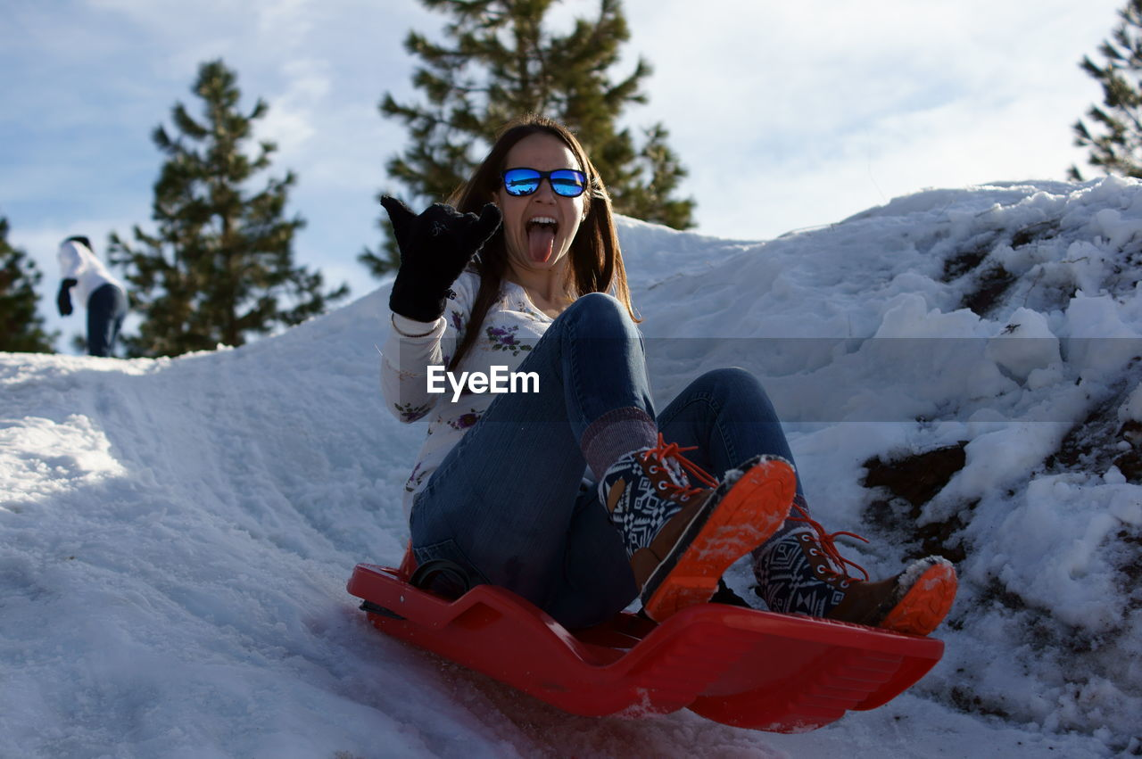 Cheerful woman sitting in sled on snow covered mountain against sky
