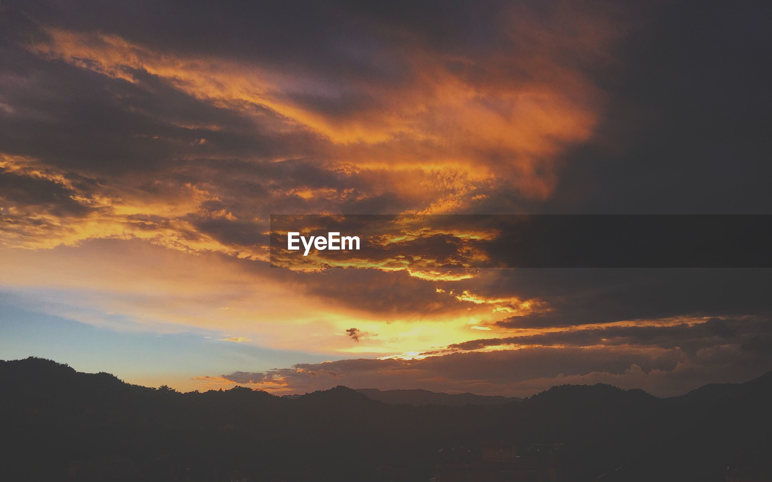 Scenic view of silhouette mountains against cloudy sky at sunset