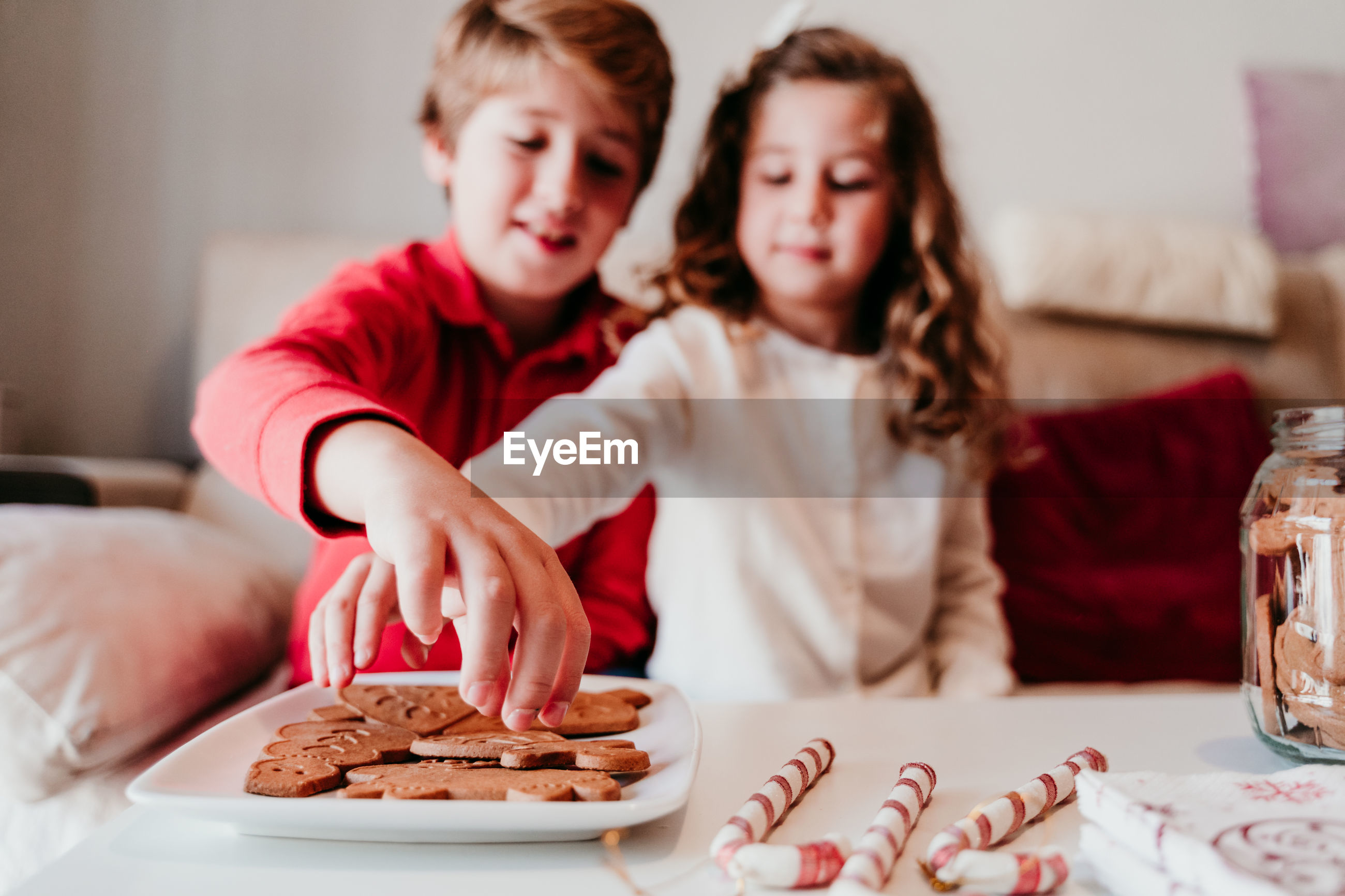 Siblings sitting by food on table at home