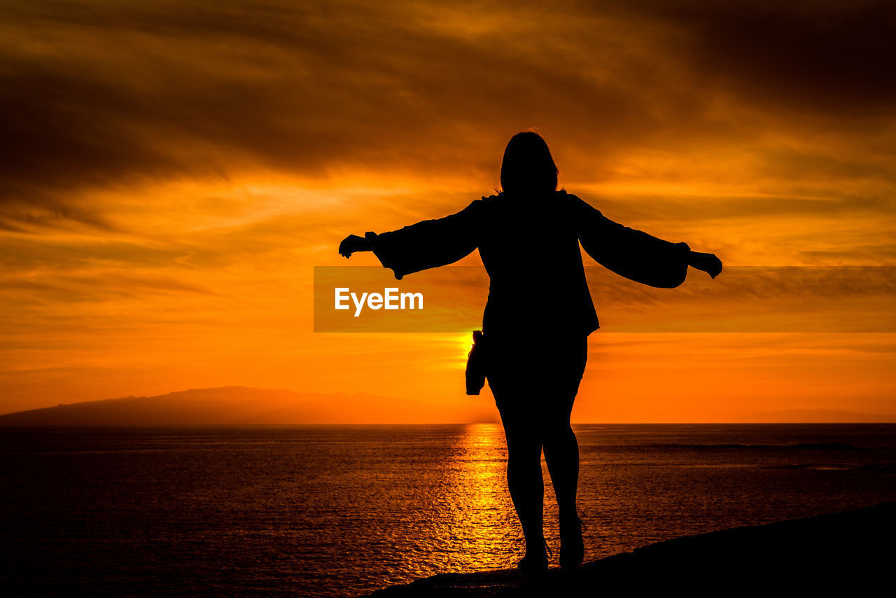 Silhouette woman standing at beach against orange sky