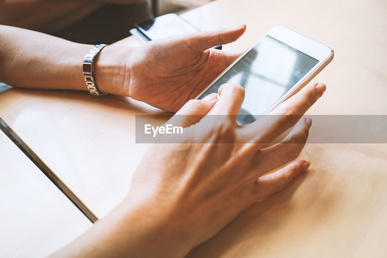 Close-up of hand using mobile phone on table