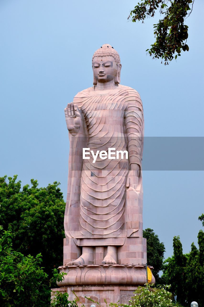 sculpture, statue, art and craft, representation, tree, male likeness, human representation, plant, sky, low angle view, nature, architecture, creativity, no people, belief, religion, spirituality, craft, day, clear sky, idol
